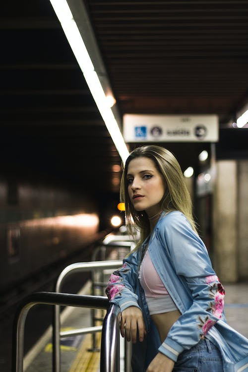 Woman Leaning on Handrail in Subway Station