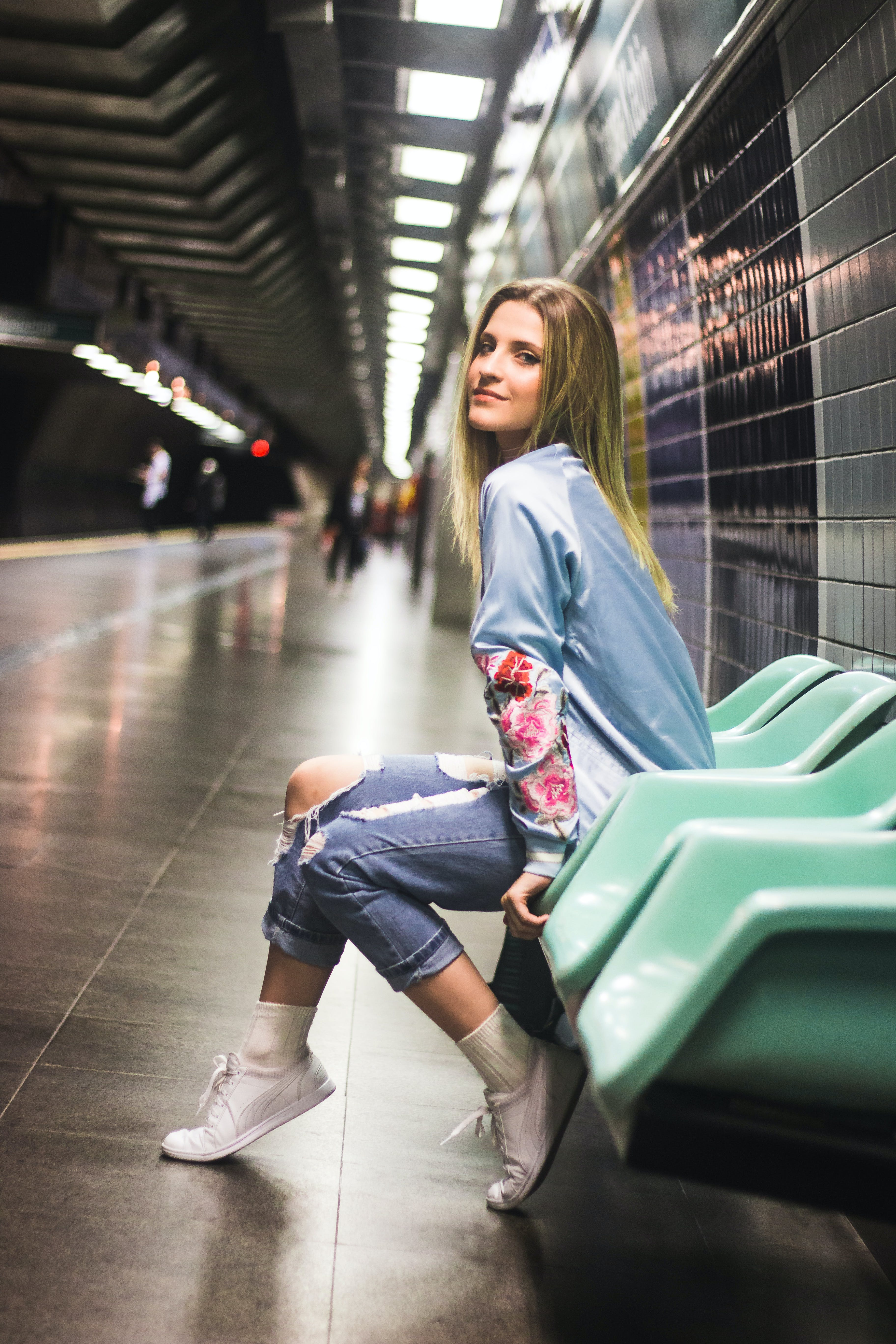 Woman Sitting on Teal Gang Chair on Train Station