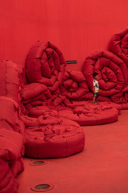 Boy in Red Jacket and Blue Denim Jeans Lying on Red Sofa