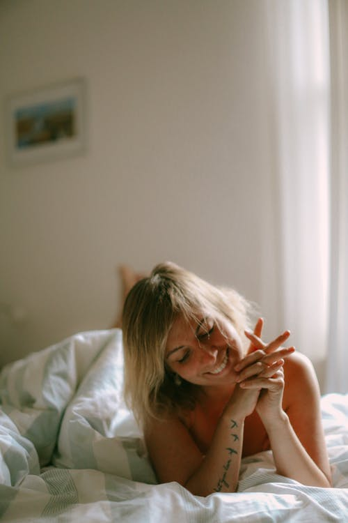 Kostenloses Stock Foto zu bett, frau, lächeln, person