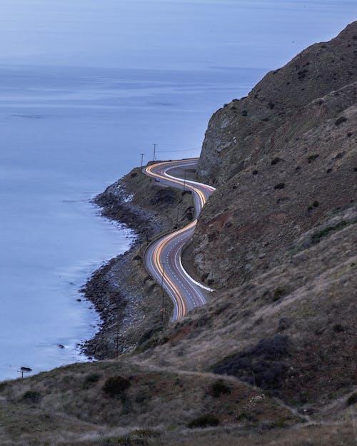 Foto d'estoc gratuïta de exposició llarga, llums de cotxe, platja, sol de vespre