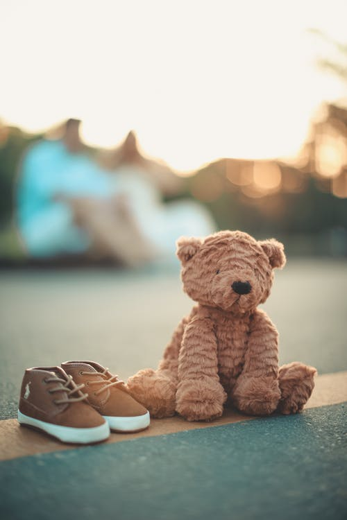 Brown Bear Plush Toy Beside Pair of Toddler's Brown-and-white Shoes on Ground in Selective Focus Photography