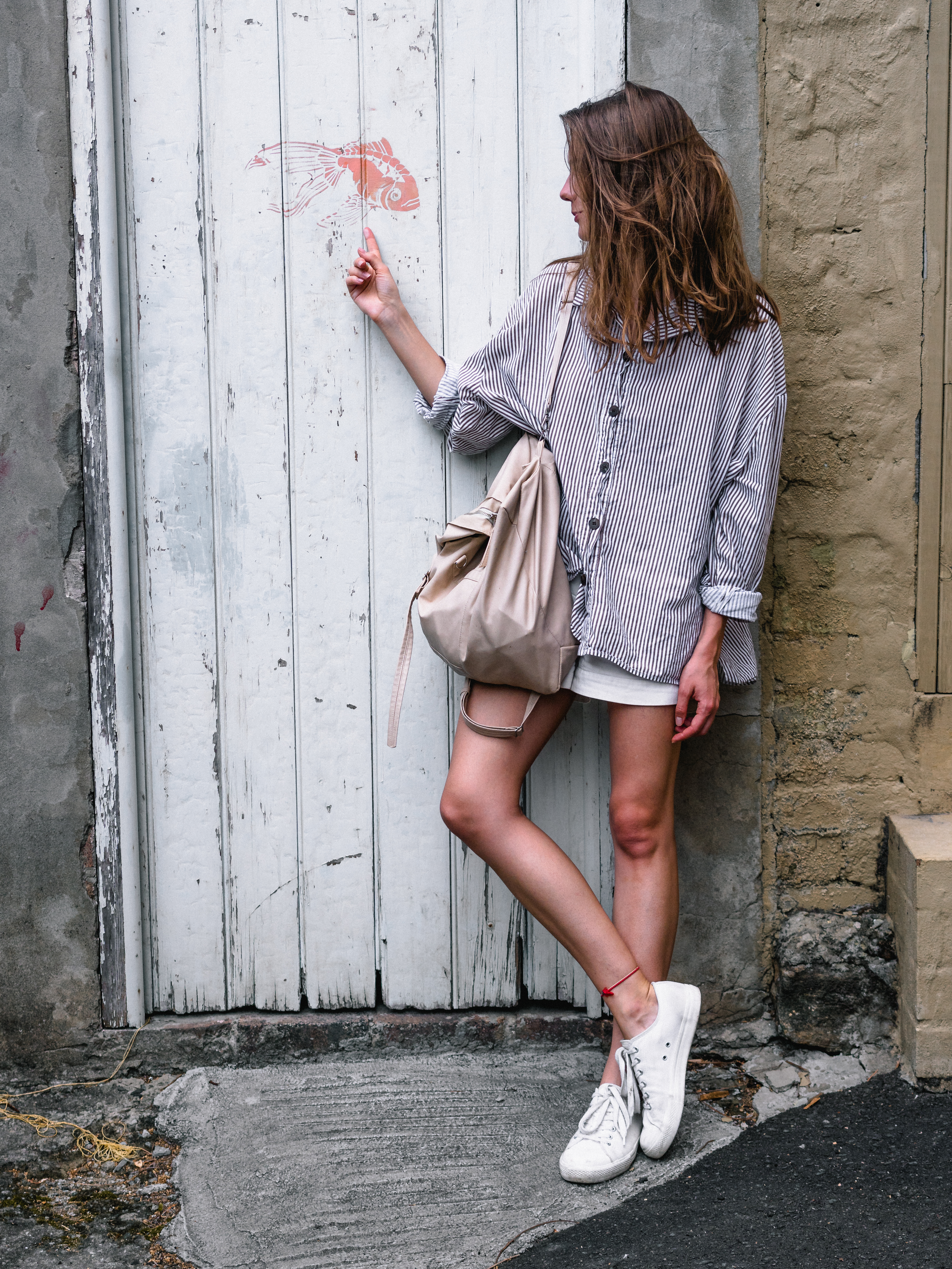 Woman Wearing Gray Long-sleeved Shirt Looking Side While Leaning on Wall