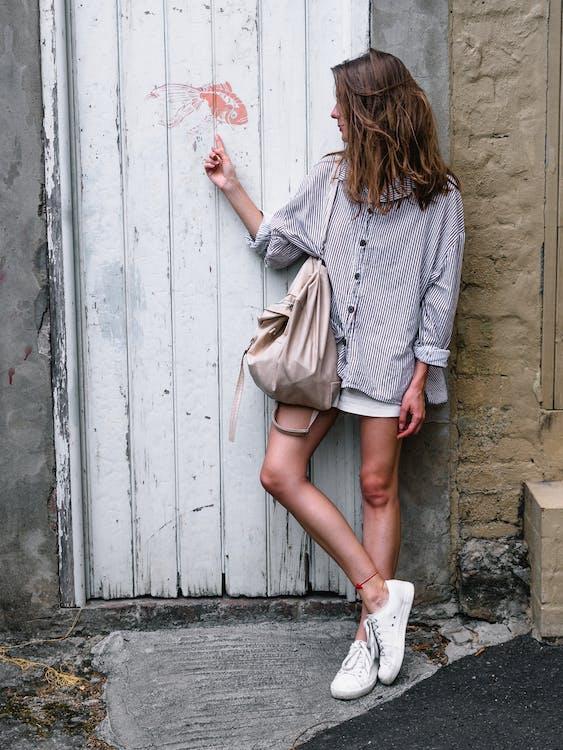 Mulher Vestindo Uma Camisa Cinza De Mangas Compridas Olhando De Lado Enquanto Se Inclina Na Parede