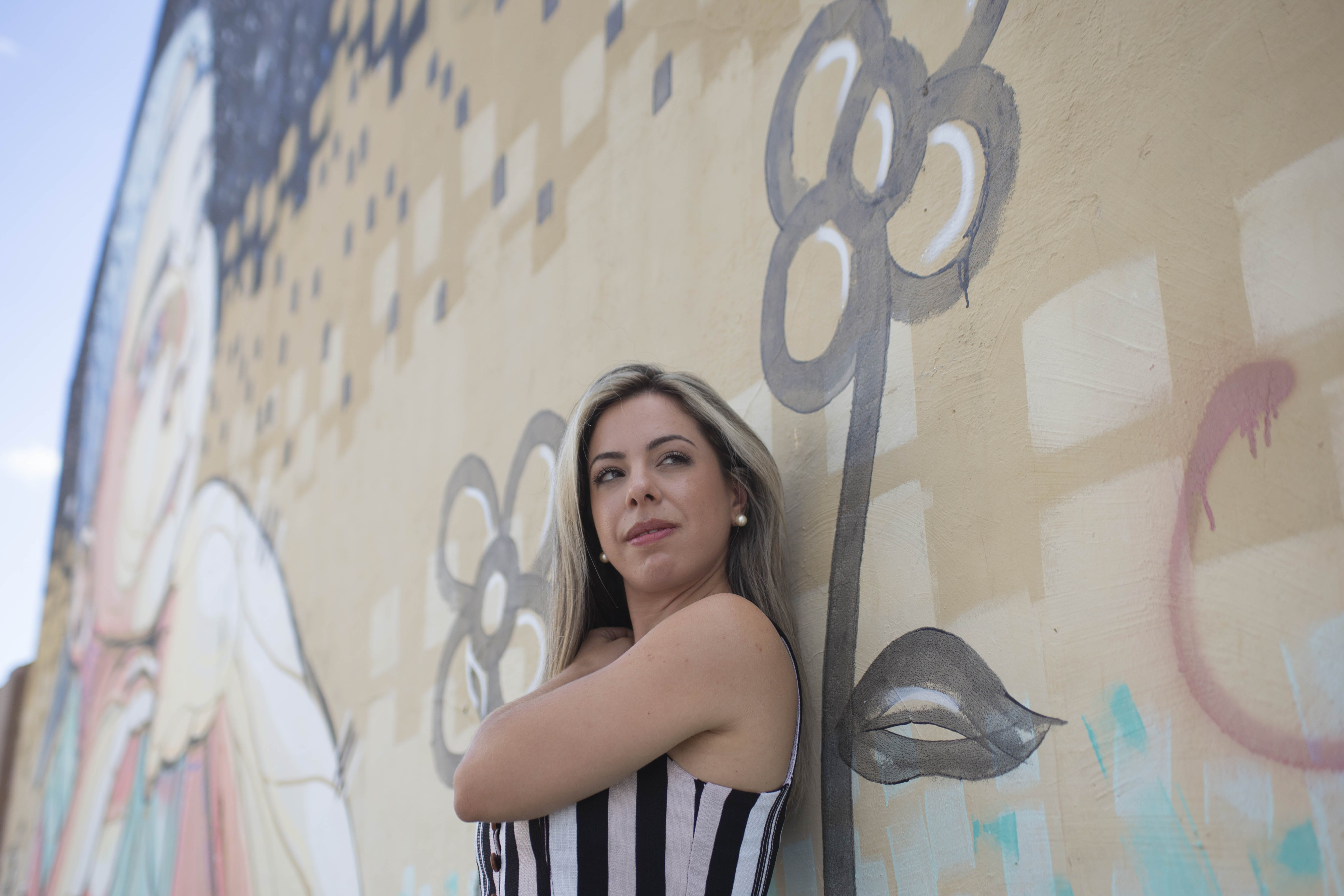 Standing Woman While Leaning on Graffiti Wall