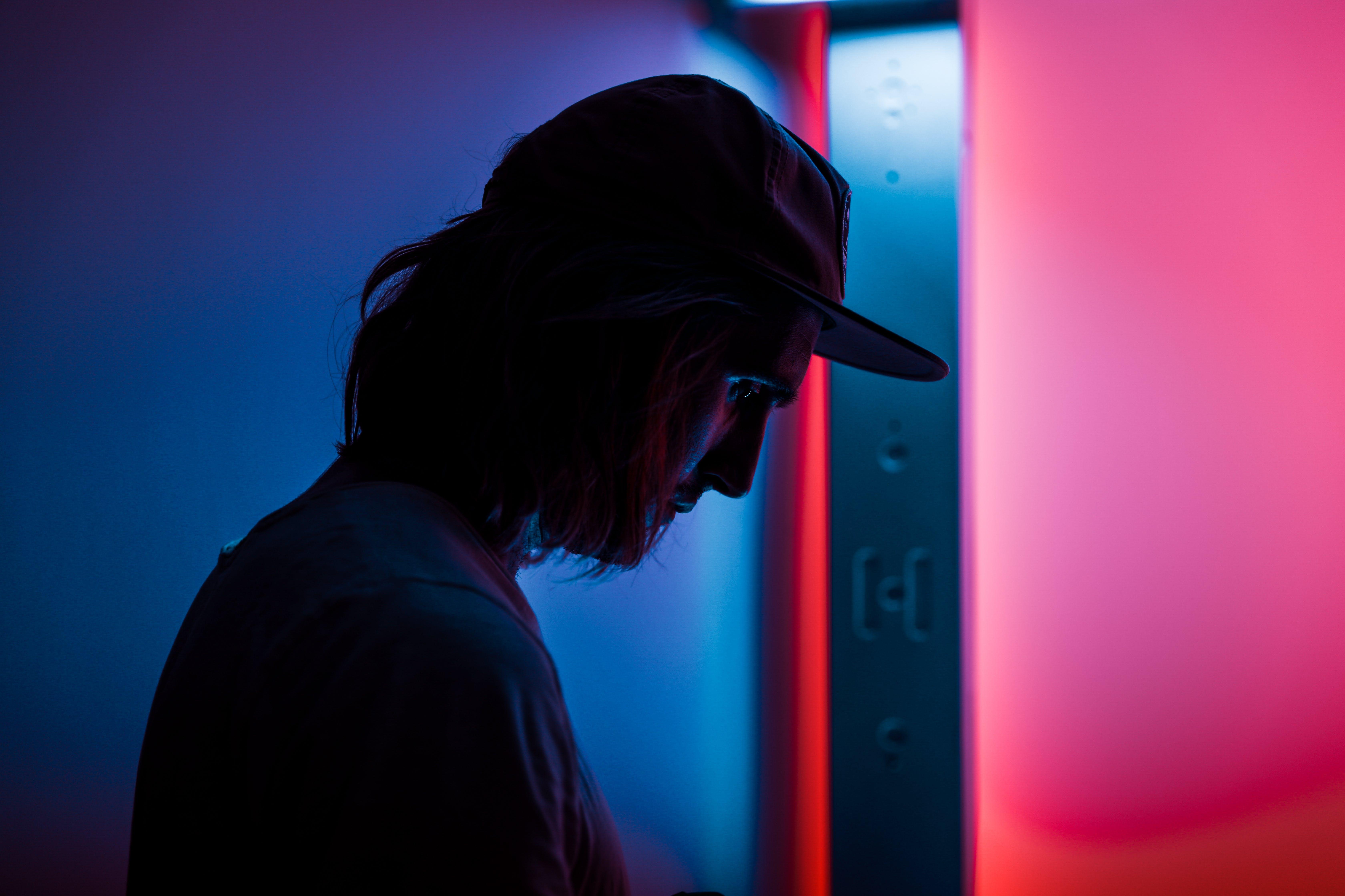 Silhouette of Man Wearing Fitted Cap Near Door