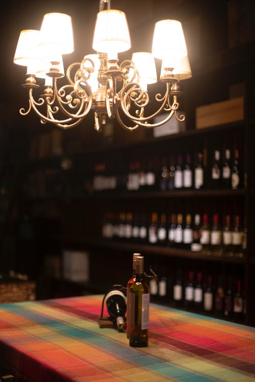 Three Wine Bottles Under Turned-on Chandelier