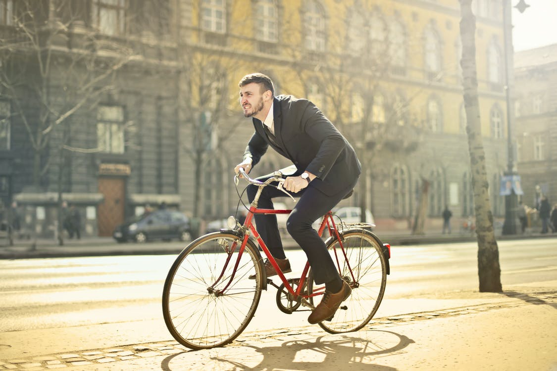 Man In Black Suit Riding Bicycle Down The Street