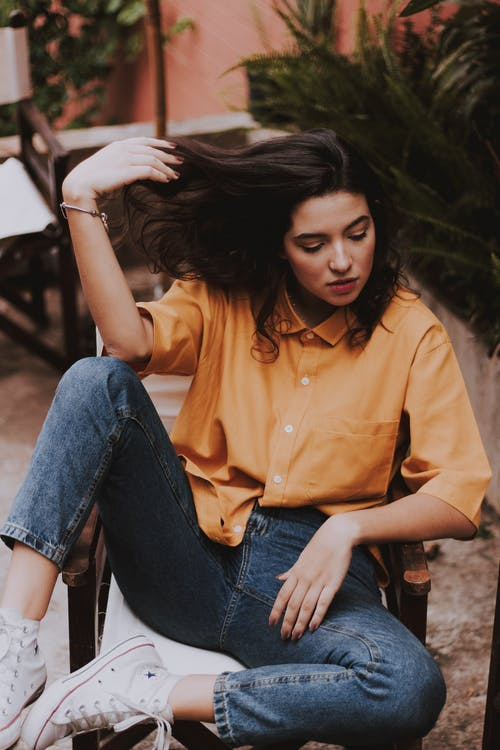 Woman Sitting on Wooden Chair While Holding Her Hair