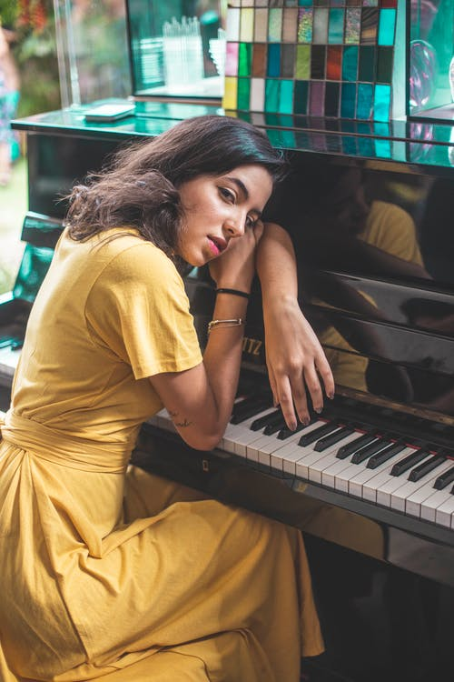 Woman Leaning on Black Piano Posing