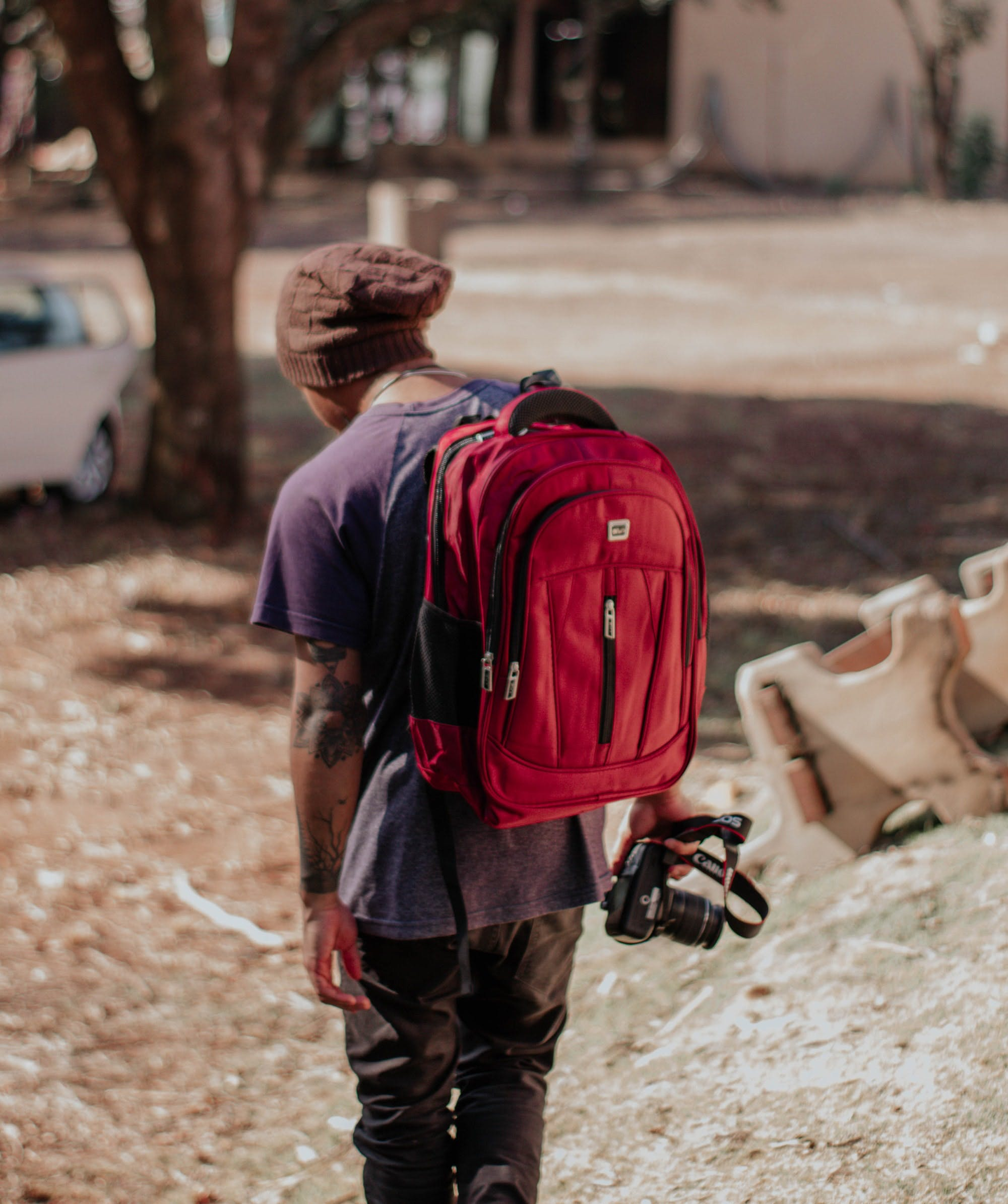 Man Holding Camera Using Red Backpack