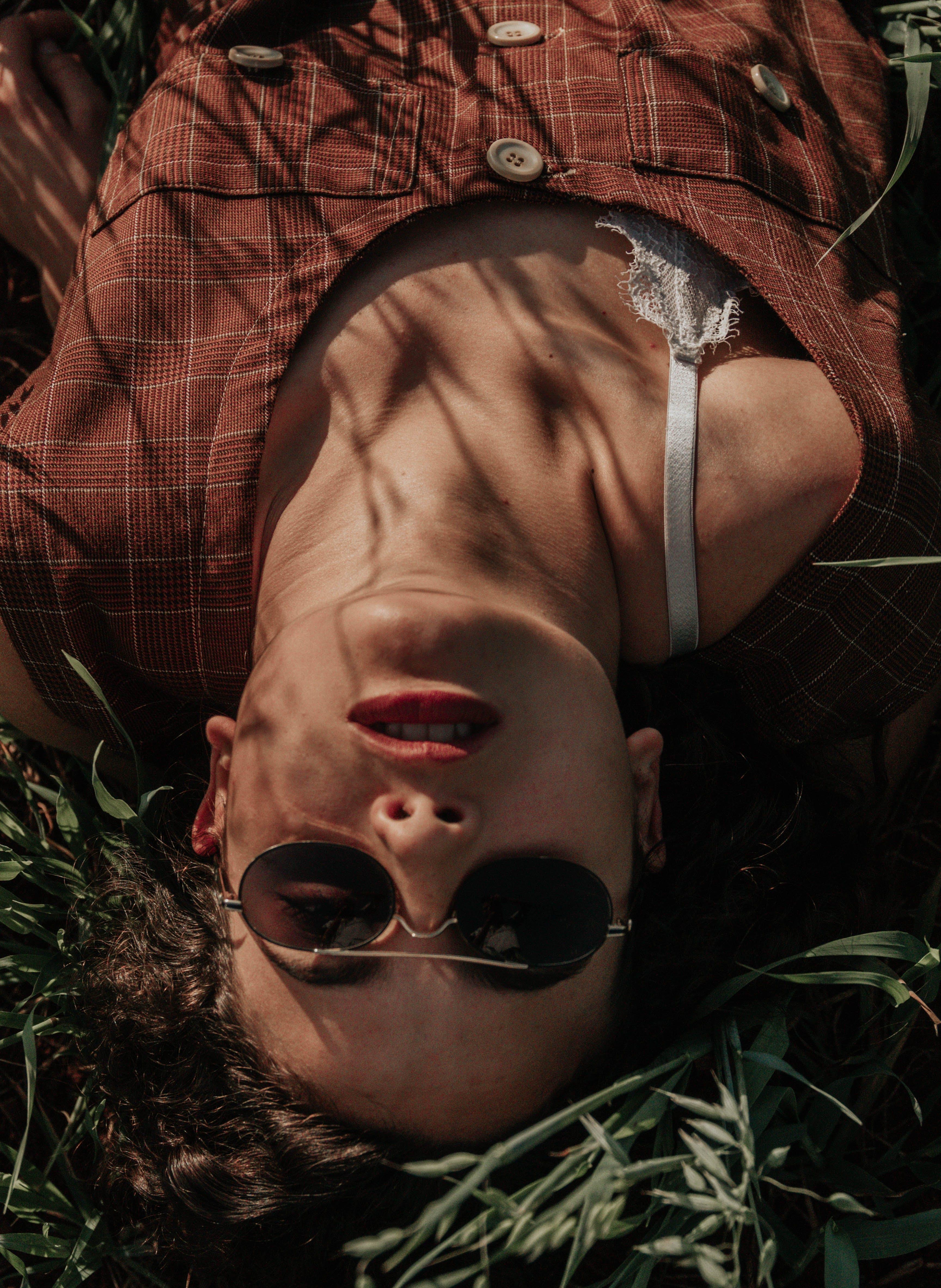 Woman Wearing Sunglasses Lying on Ground