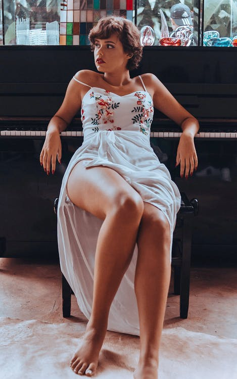 Woman Sitting Beside Upright Piano Looking Sideward