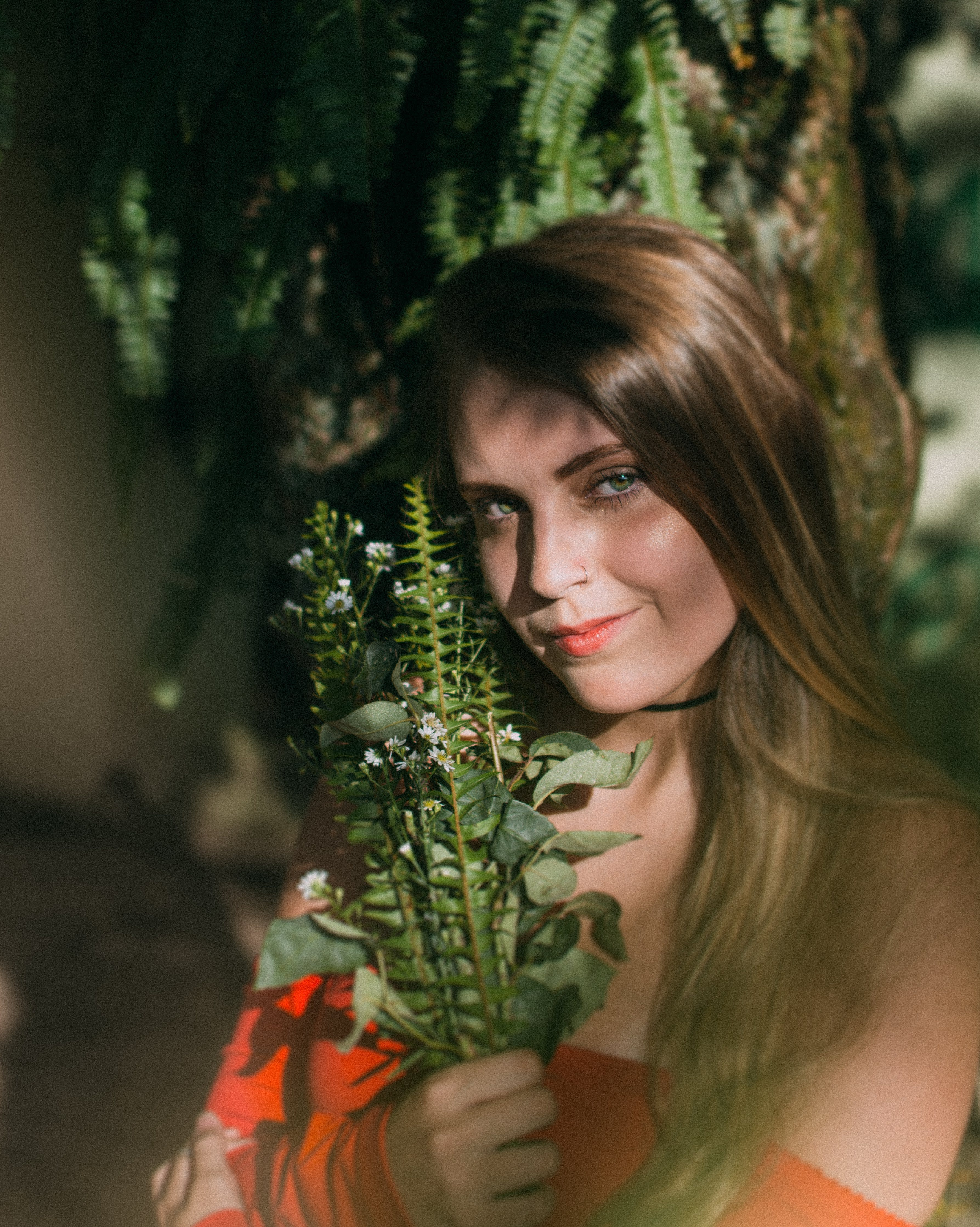 Smiling Woman Leaning On Tree Holding Plants