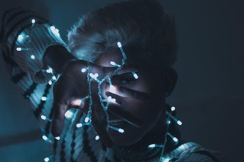 Základová fotografie zdarma na téma mobilní výzva, osoba, osvětlený, světelné řetězy