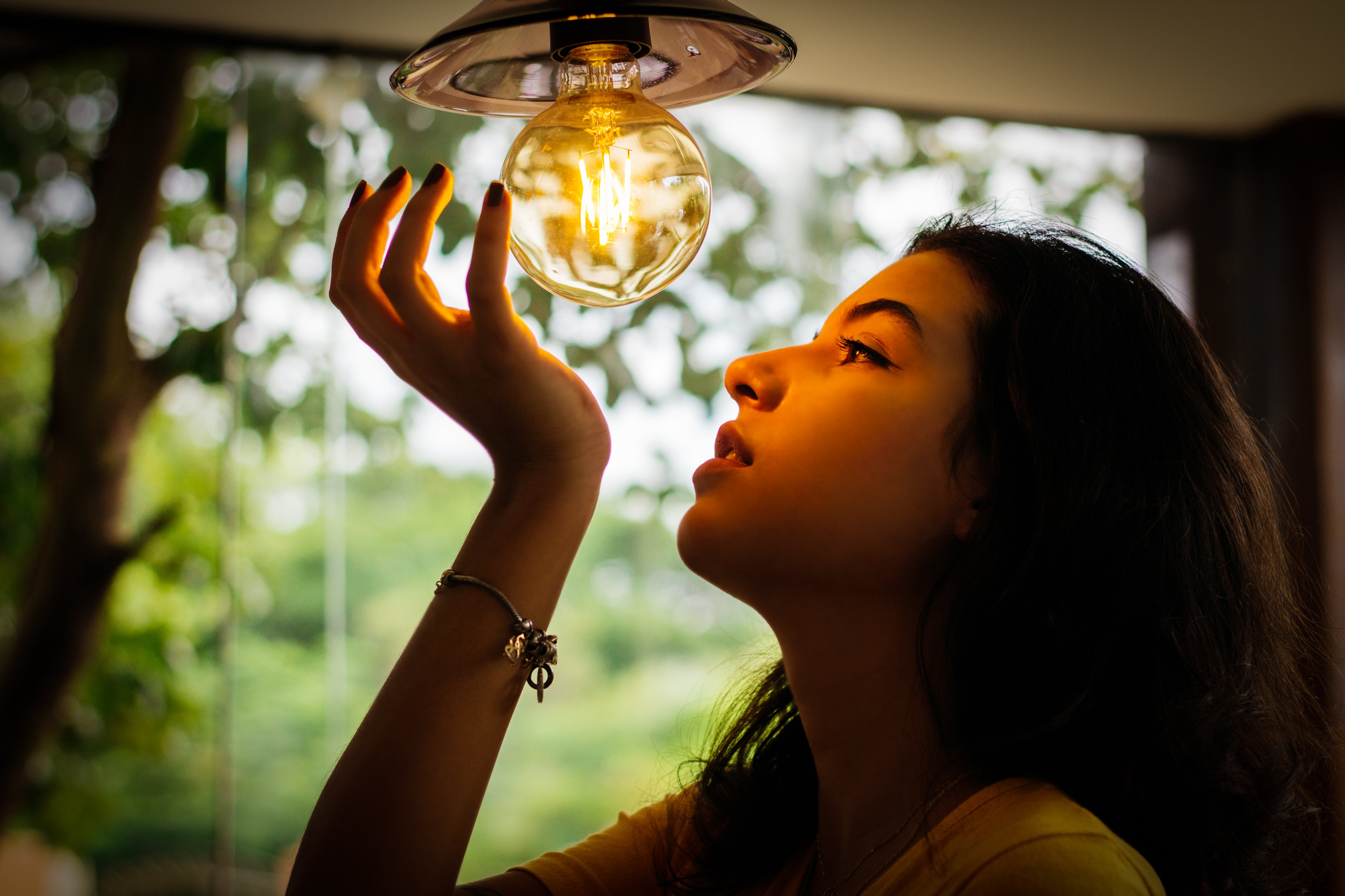 Woman Looking And Touching Bulb