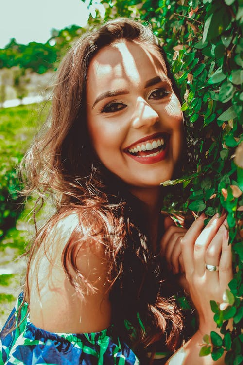 Woman Smiling Standing Next To Leaves