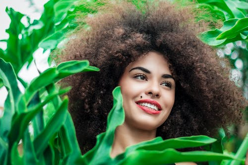 Smiling Woman Beside Green Leafed Plants