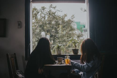Two Women Sitting at Table Near Window