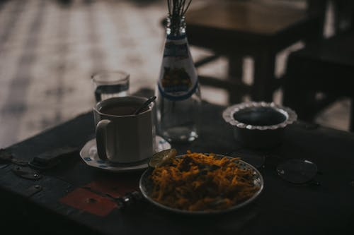 Cup Bottle and Food on Table Close-up Photo