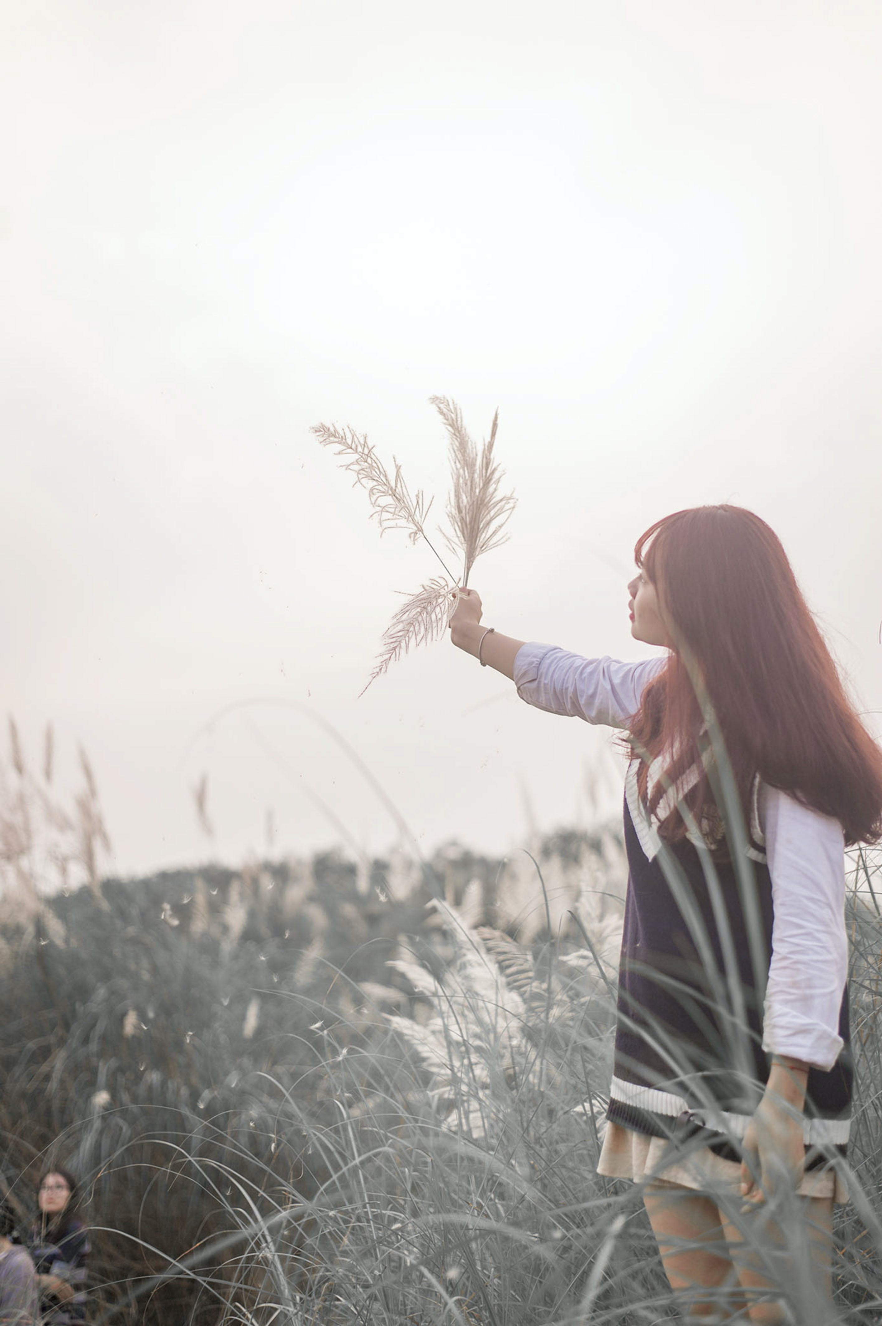 Woman Raising Right Arm With Grasses