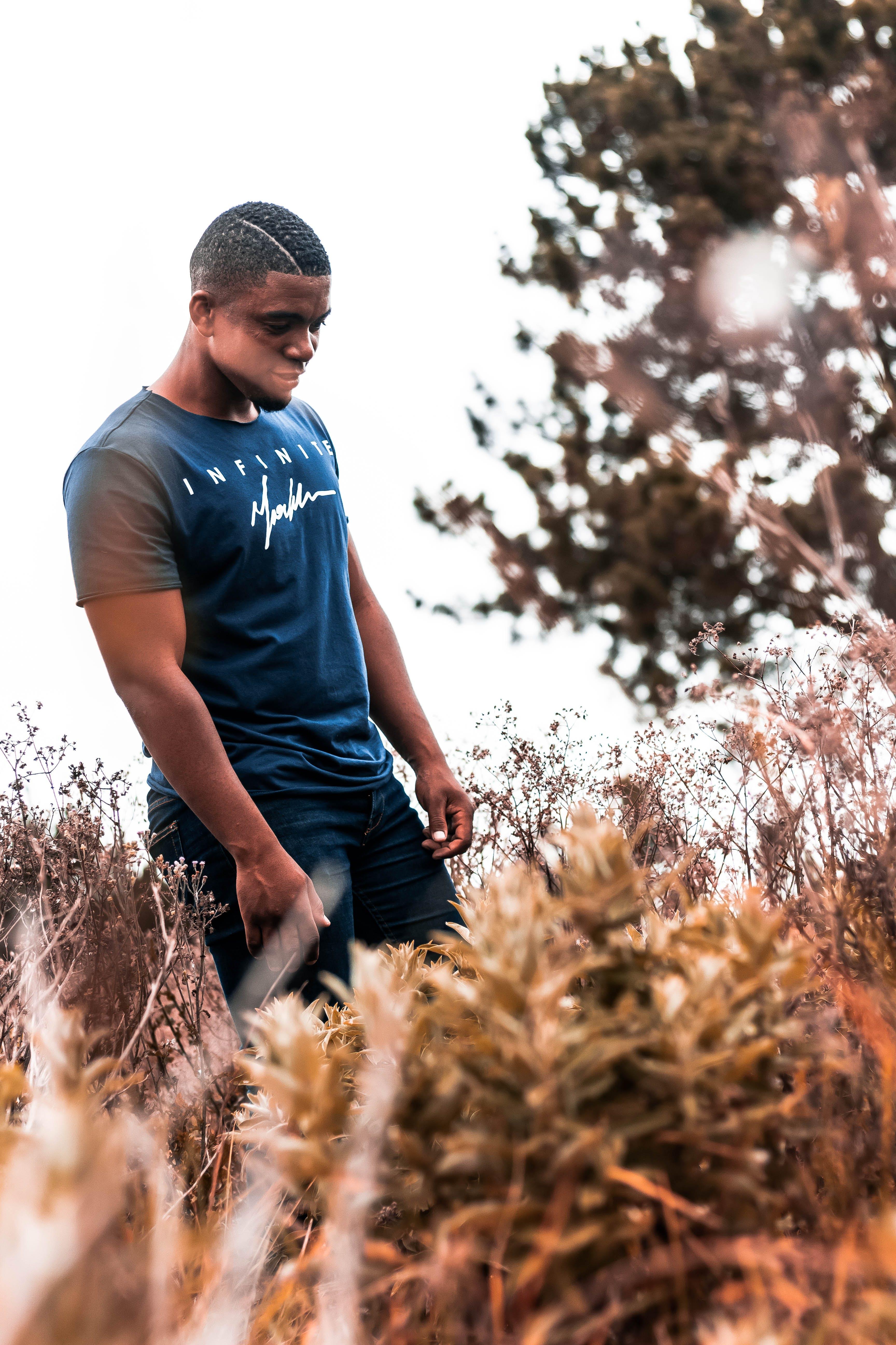 Man Wearing Blue Crew-neck T-shirt Standing Near the Tree Outdoor