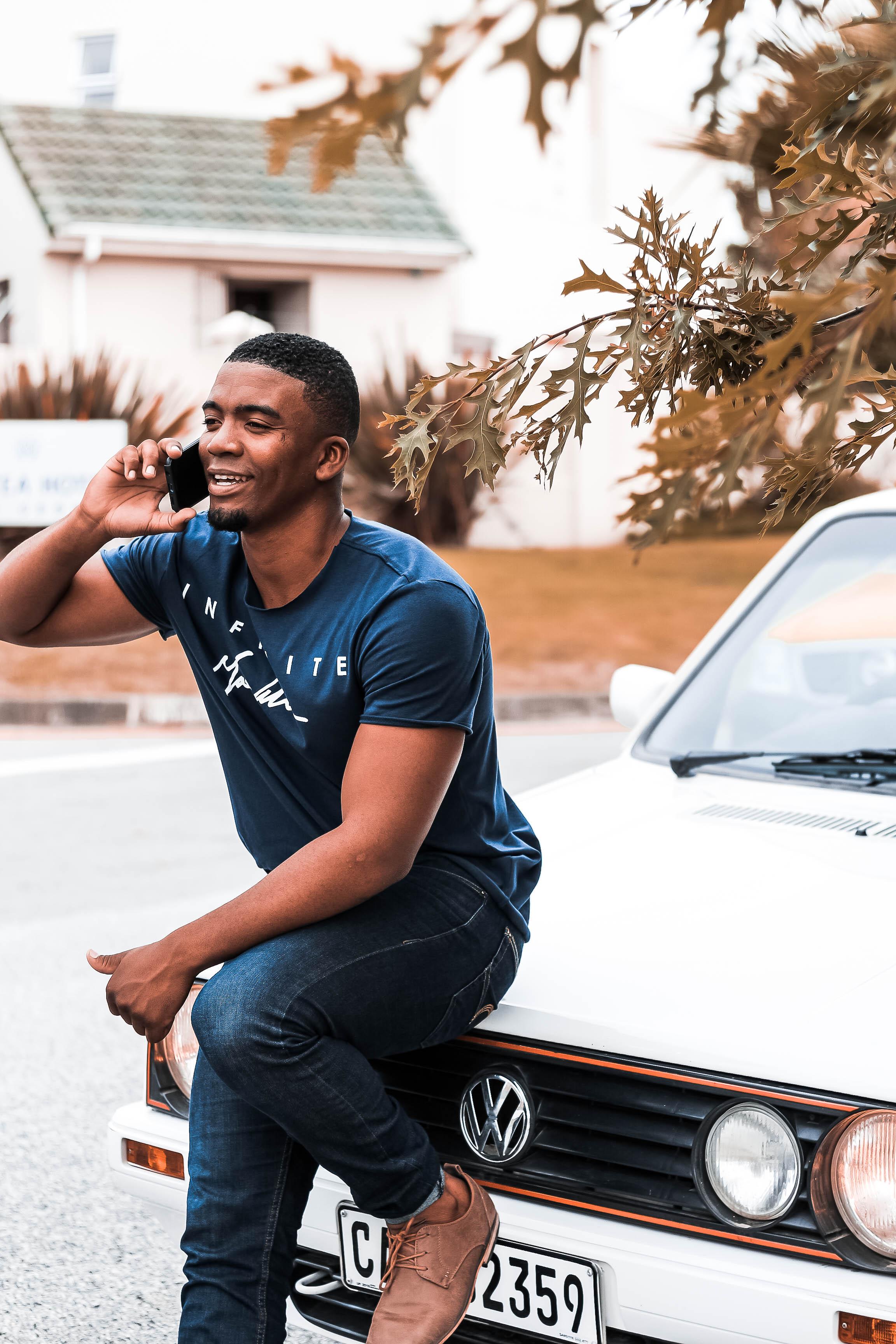 Man Holding Smartphone White Leaning on Vehicle