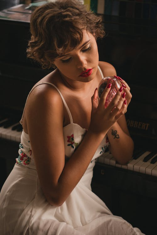 Woman Holding Crystal Ball Sitting Beside Piano