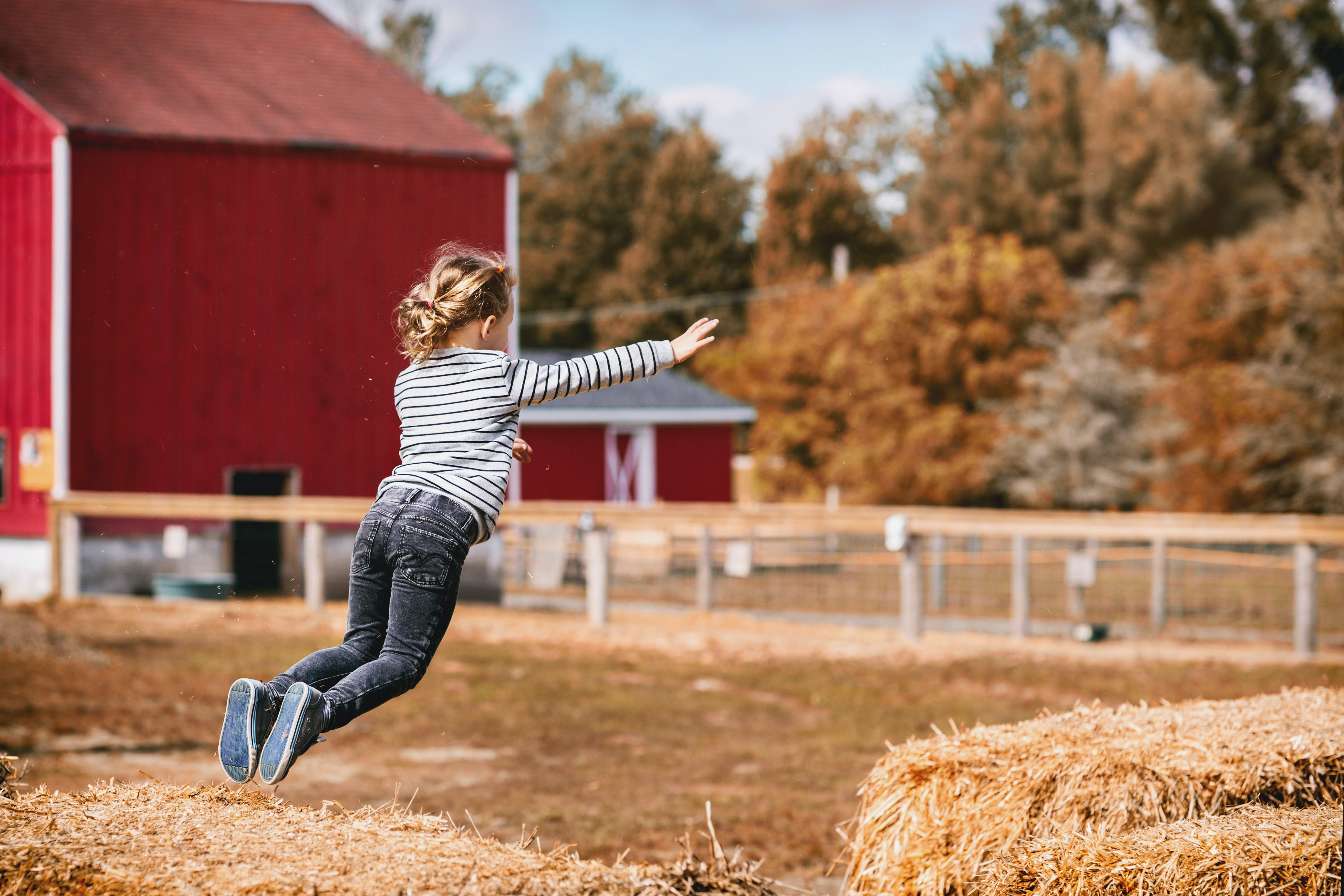 Girl Wearing White and Black Striped Long-sleeved Shirt Jumping Outdoor