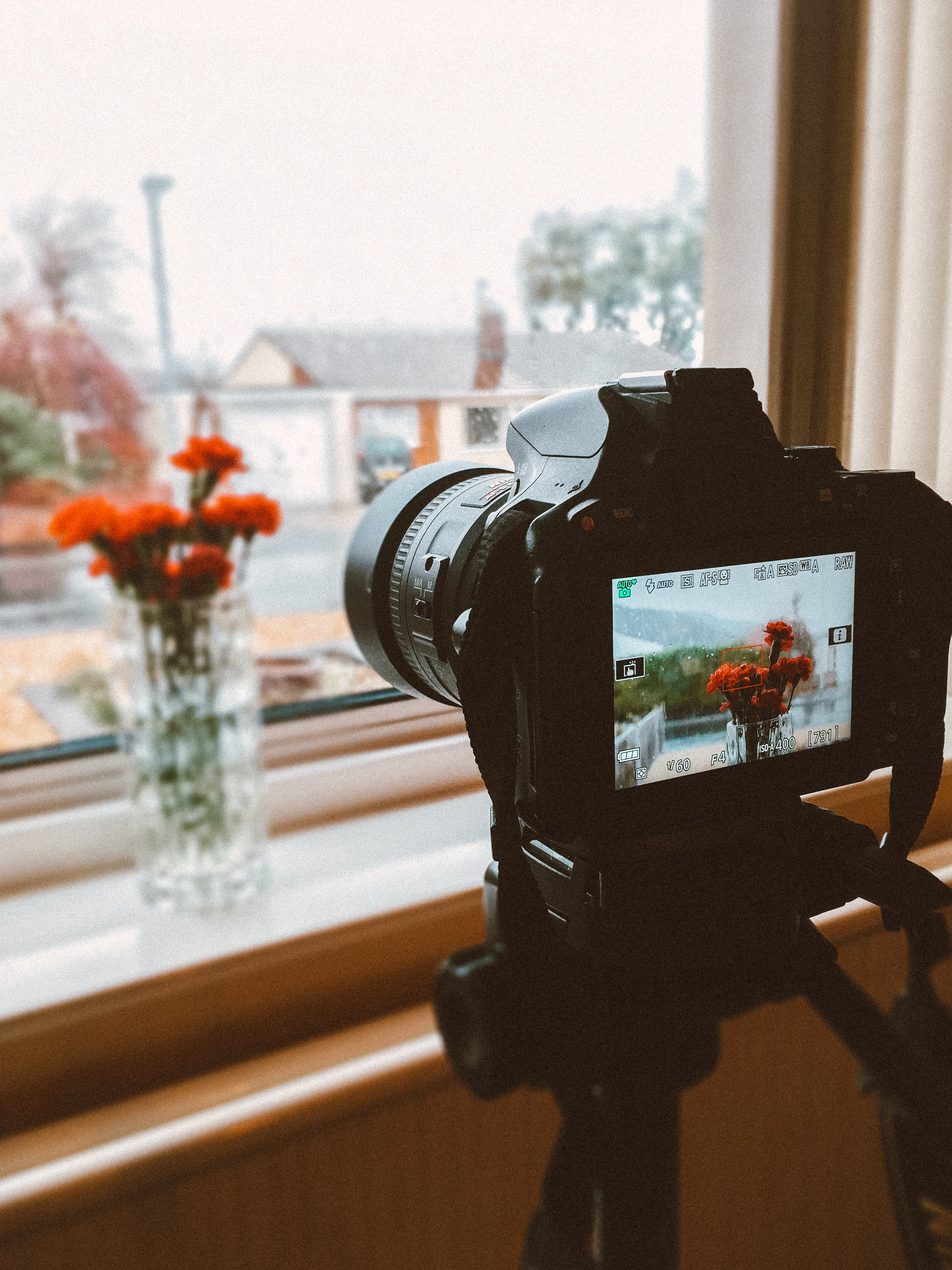 Black Dslr Camera Taking Photo of Orange Flowers in Clear Glass Flower Vase