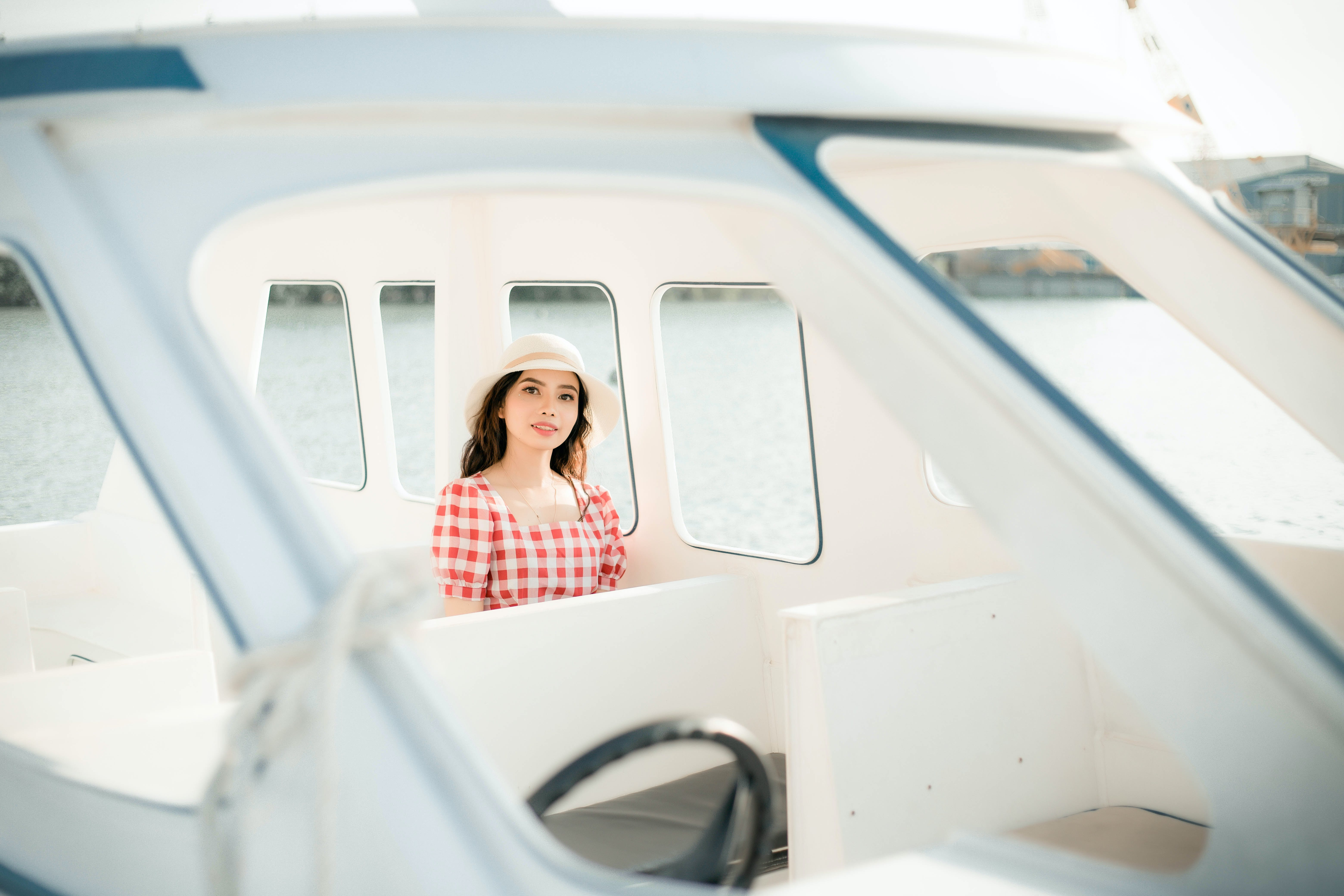 Woman Wearing Hat And Gingham Top Sitting In Powerboat