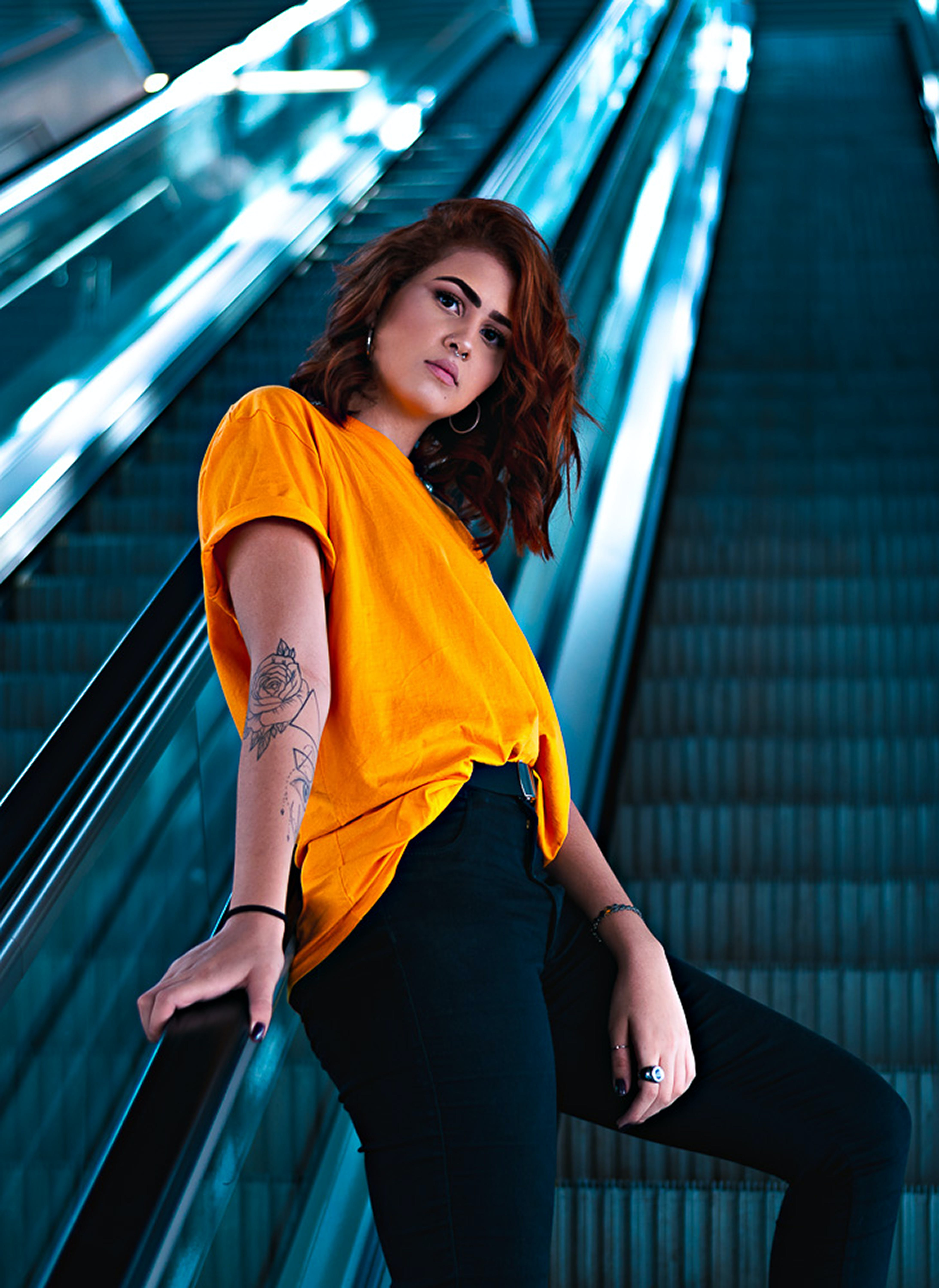 Selective Focus Photography Of Woman Wearing Yellow T-shirt On Escalator
