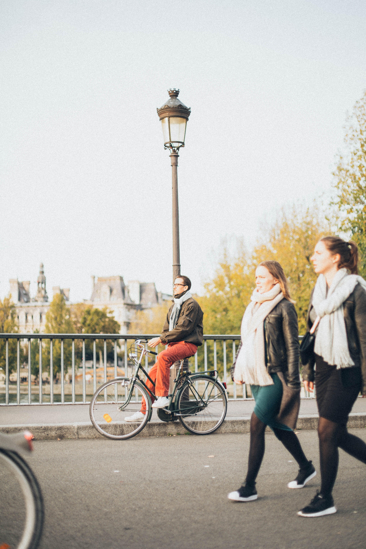 2 Woman Walking Near Man Riding Bike Near Lamp Post