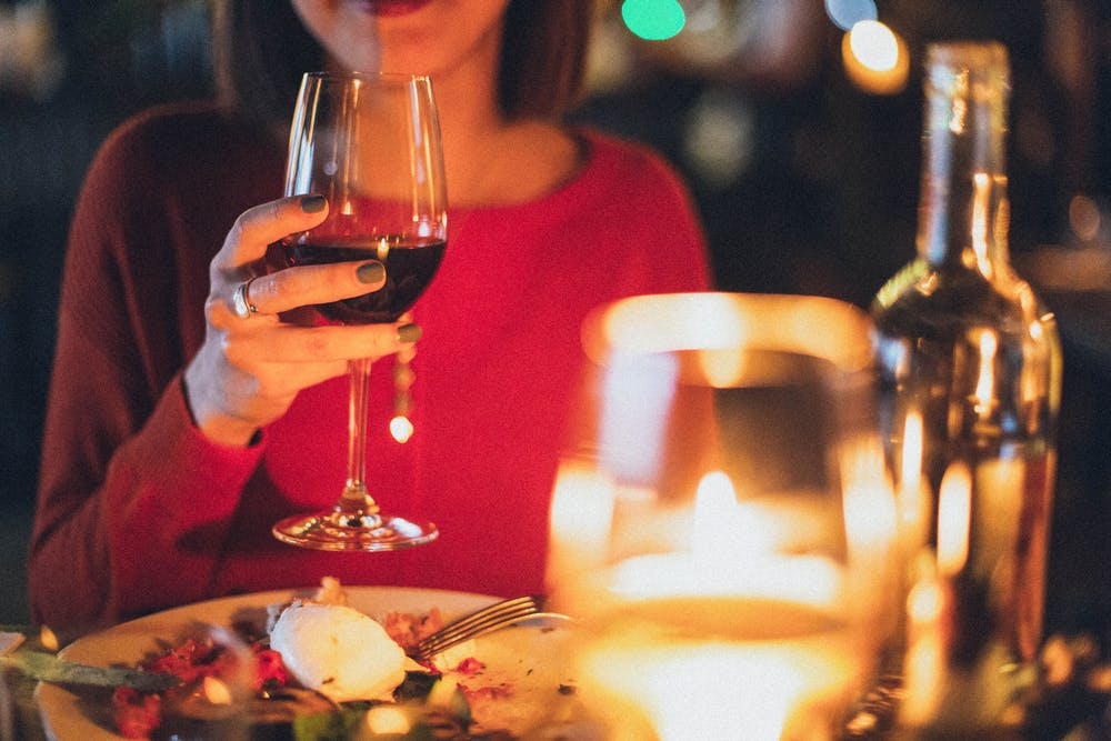 Woman holding wine glass   Photo: Pexels