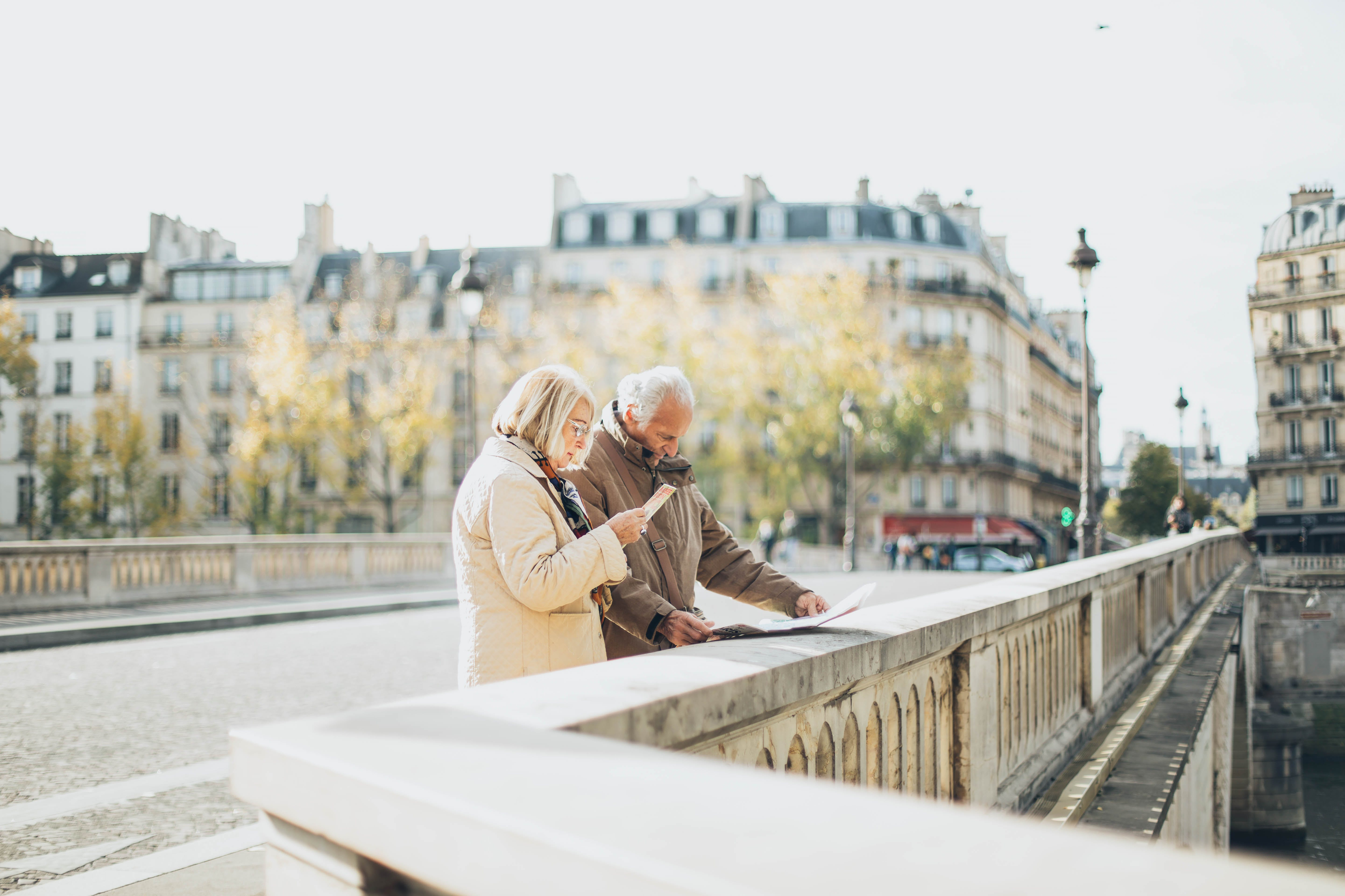 Man and Woman Standing Near the Road While Reading