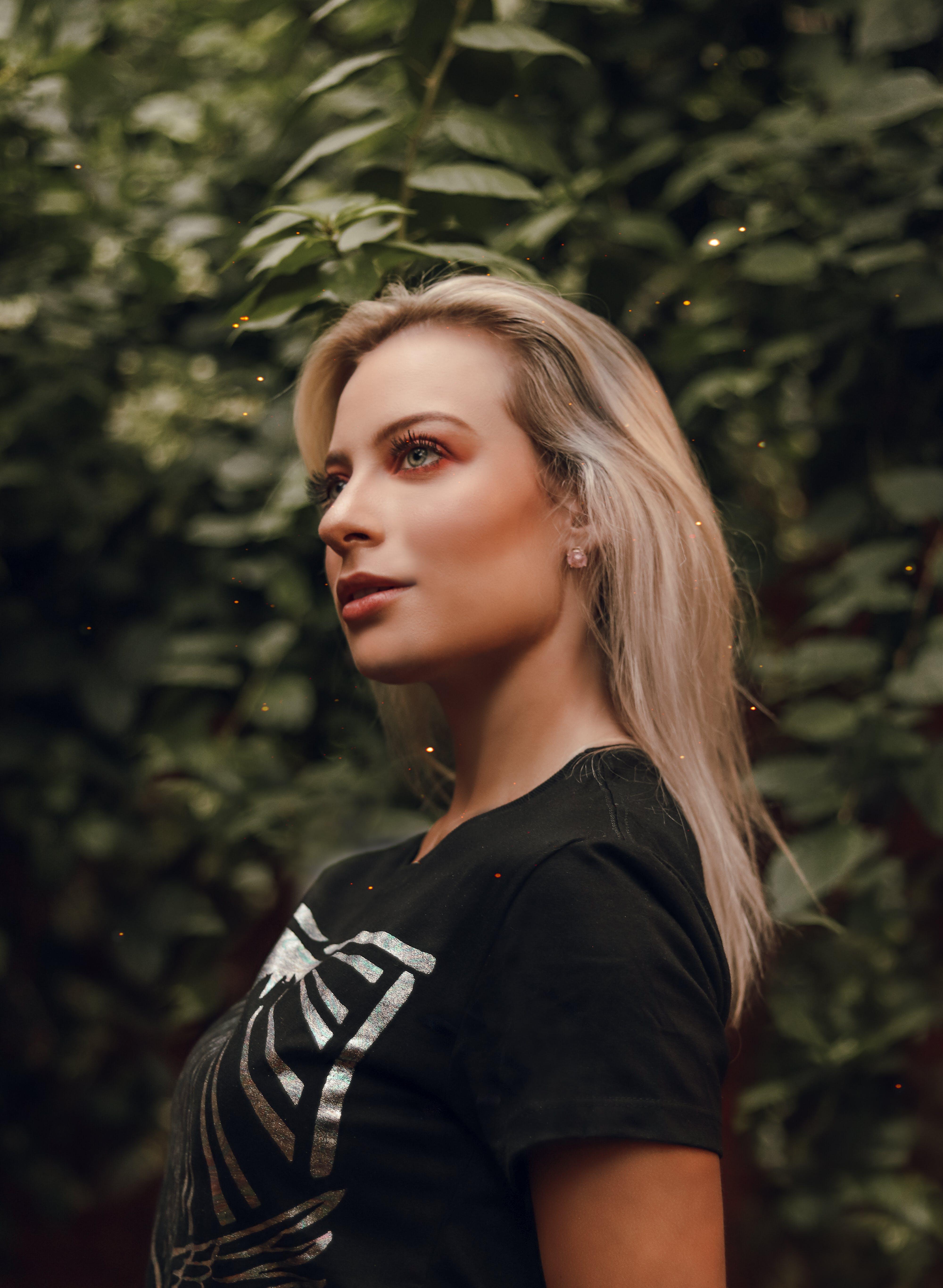 Woman in Black Crew-neck T-shirt Standing Near Green Tree