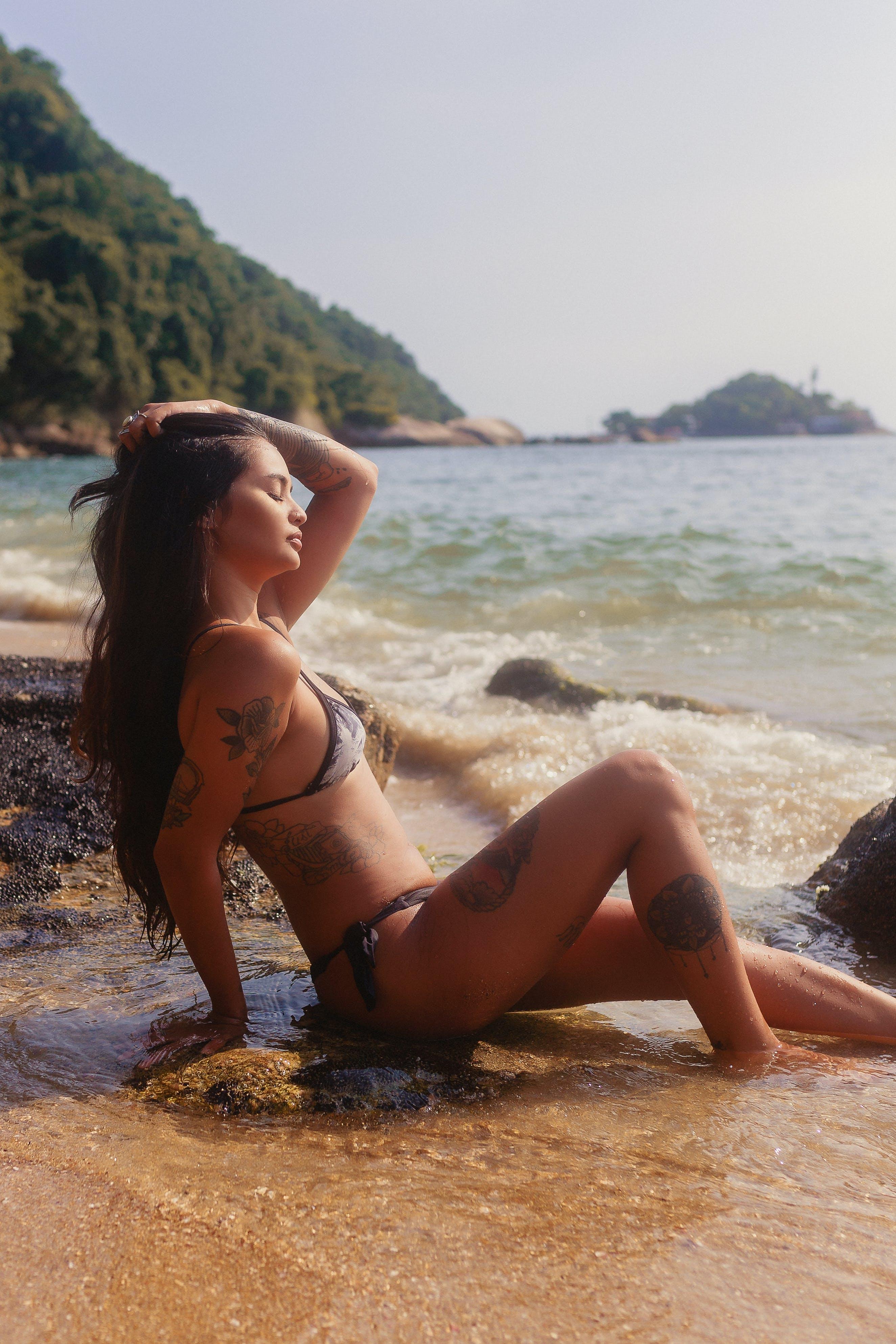 Woman in Bikini Sitting on Shore