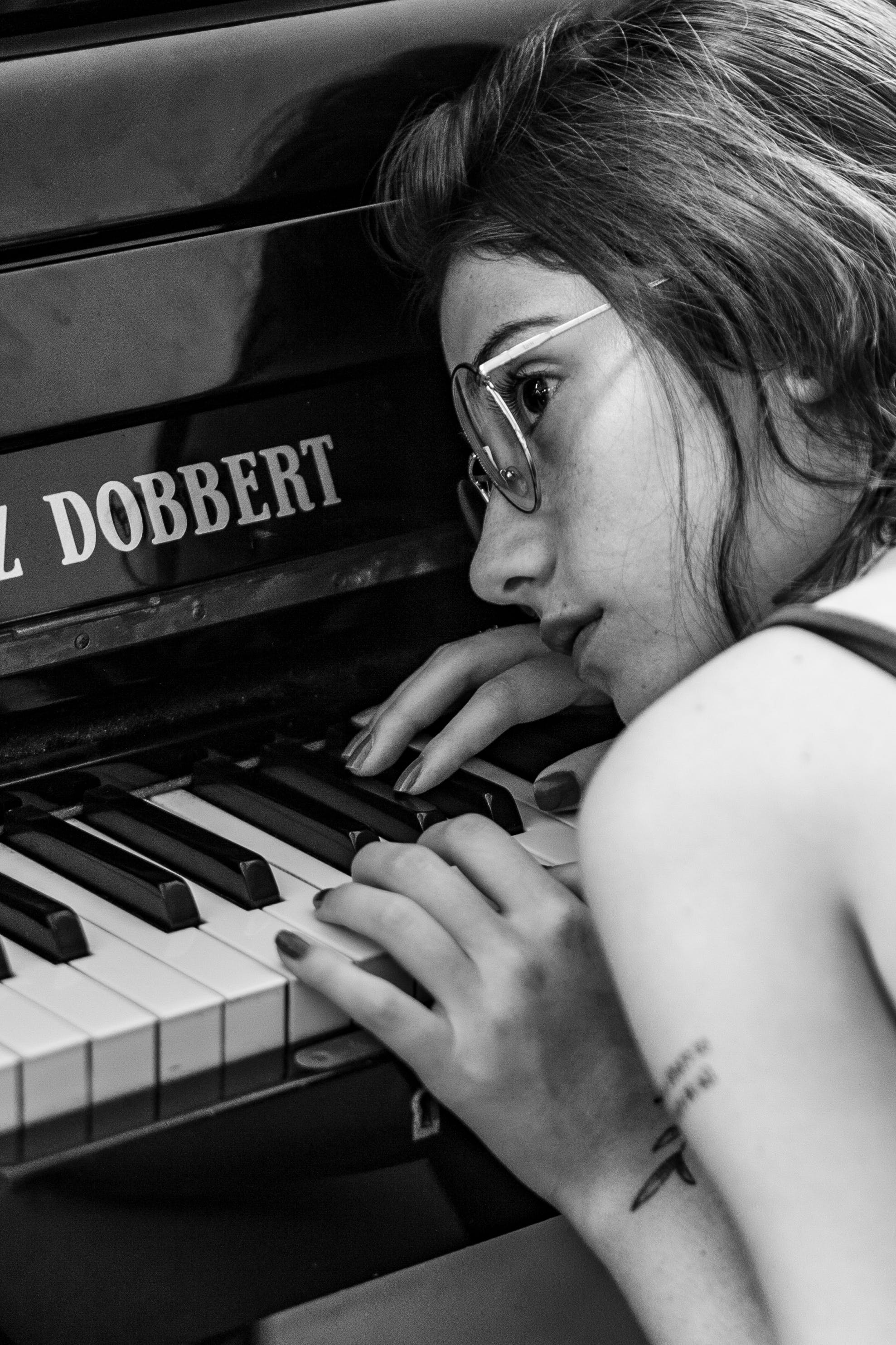 Woman Wearing Eyeglasses leaning on Piano