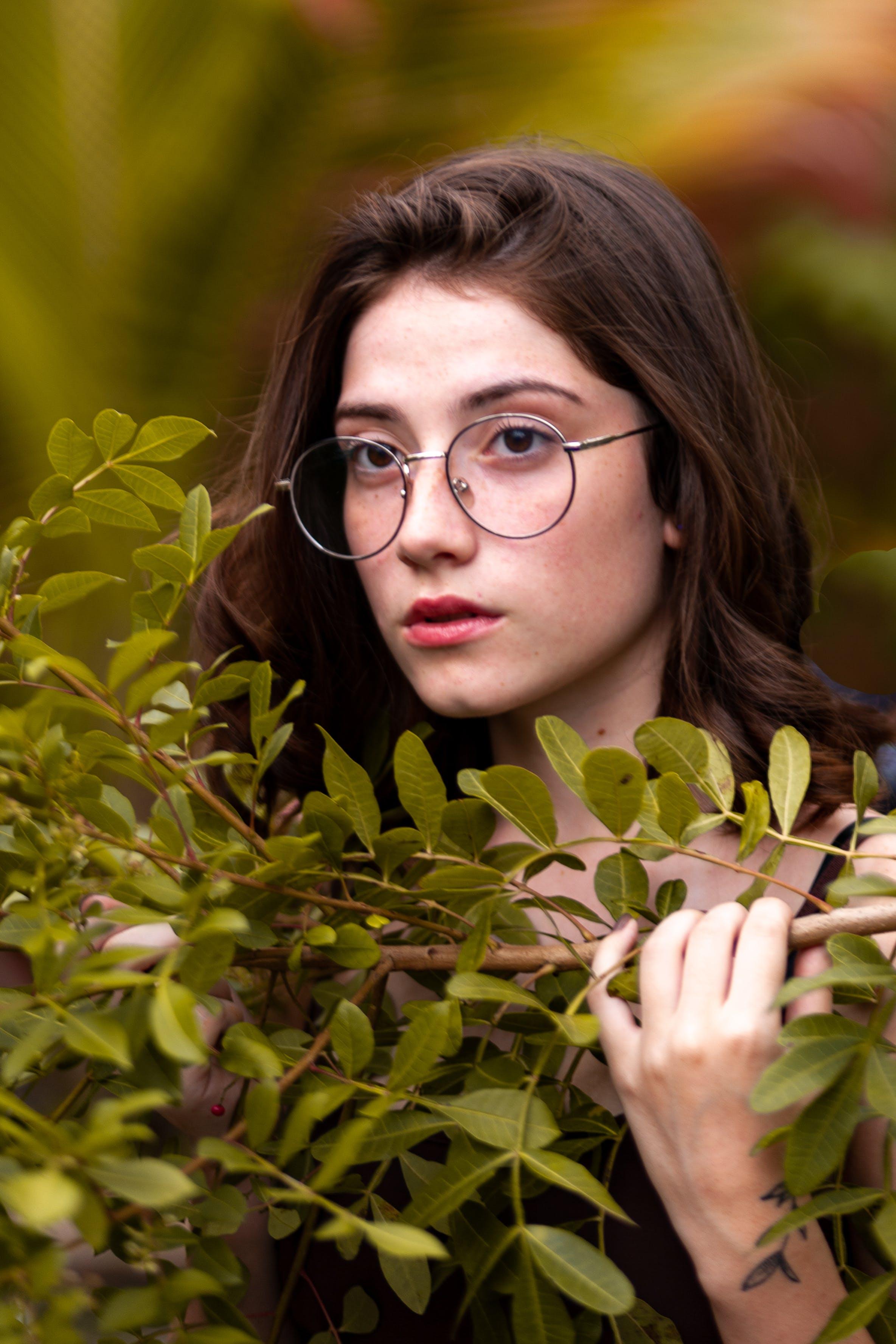 Woman Posing Behind Green Leaves