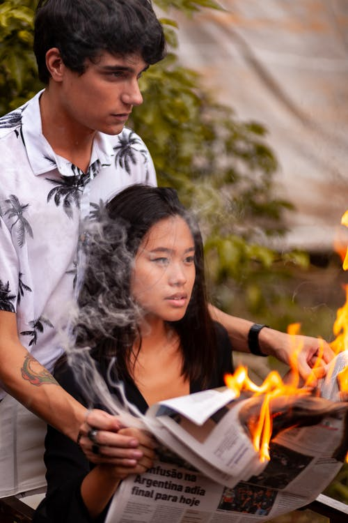Man Standing Behind Woman While Holding Her Hands With Burning Newspaper