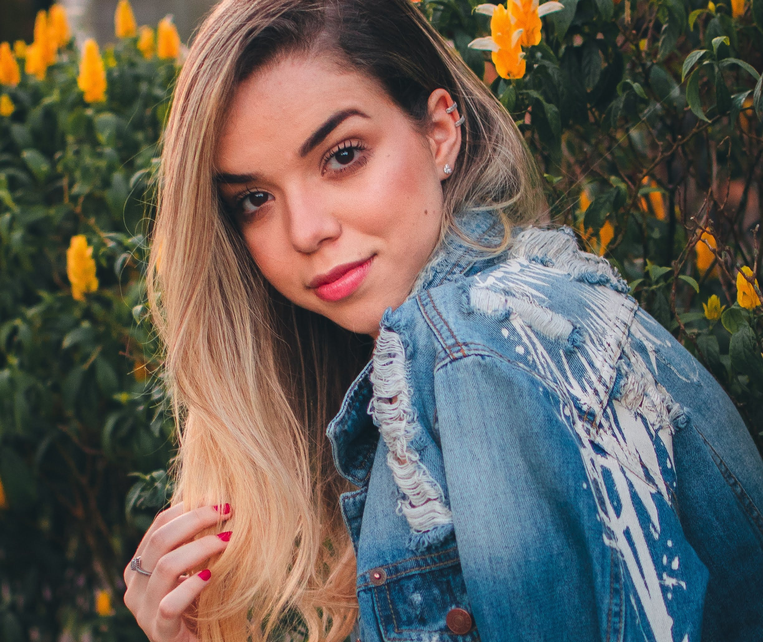 Woman Wearing Blue Denim Jacket Posing Near Yellow Petaled Flowers
