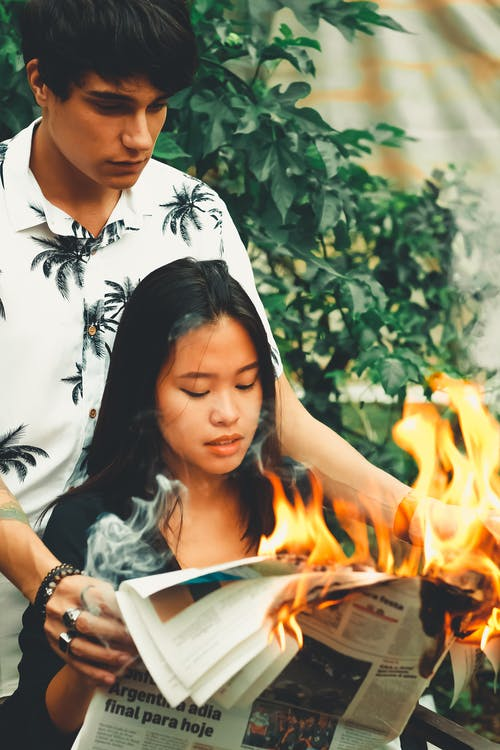 Woman and Man Holding Burning newspaper