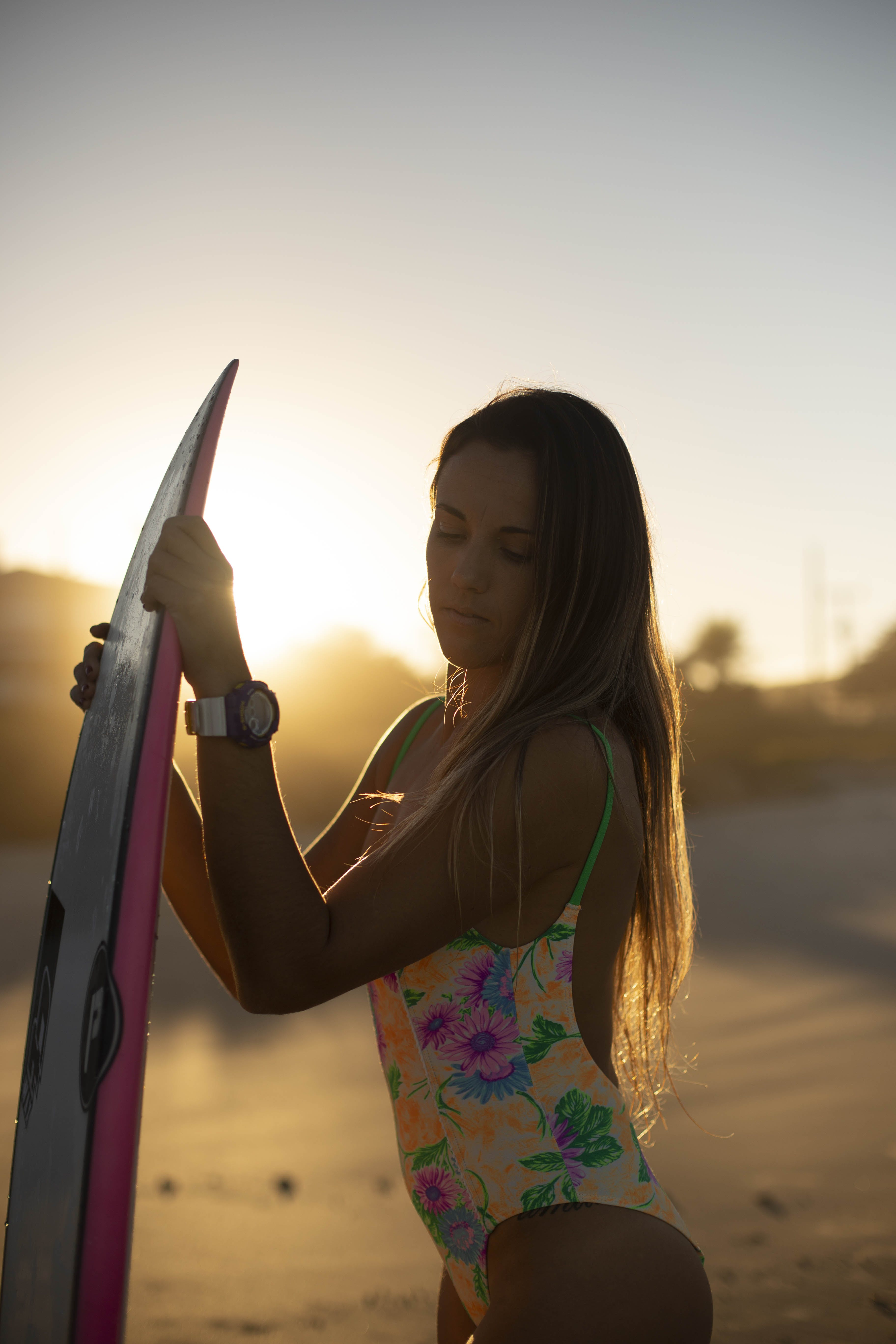 Woman in Yellow and Green Floral One-piece Swimsuit Holding Surfboard