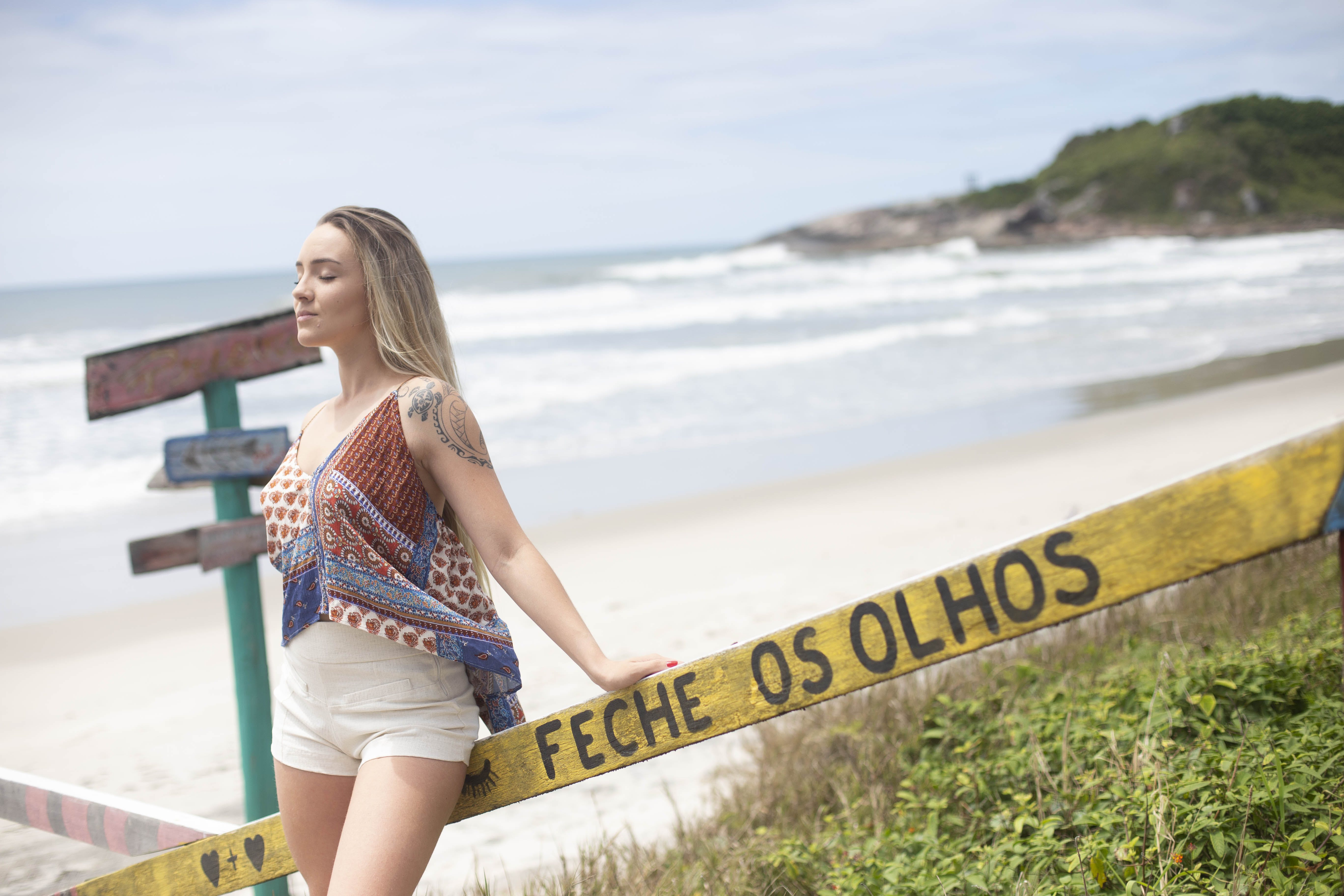 Woman Standing Beside Feche Os Olhos Signage