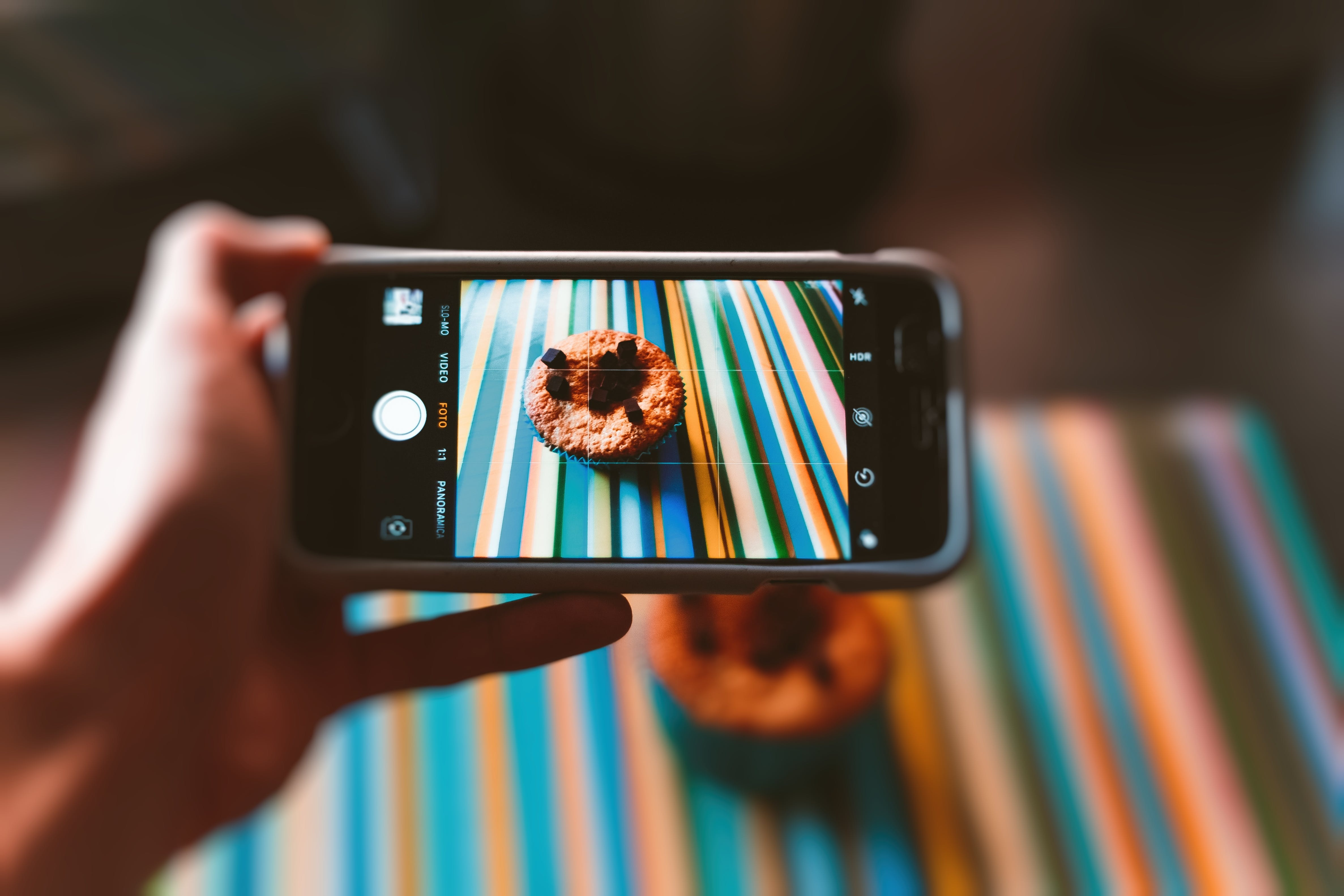 Person Taking Photo of Chocolate Cupcake Using Smartphone