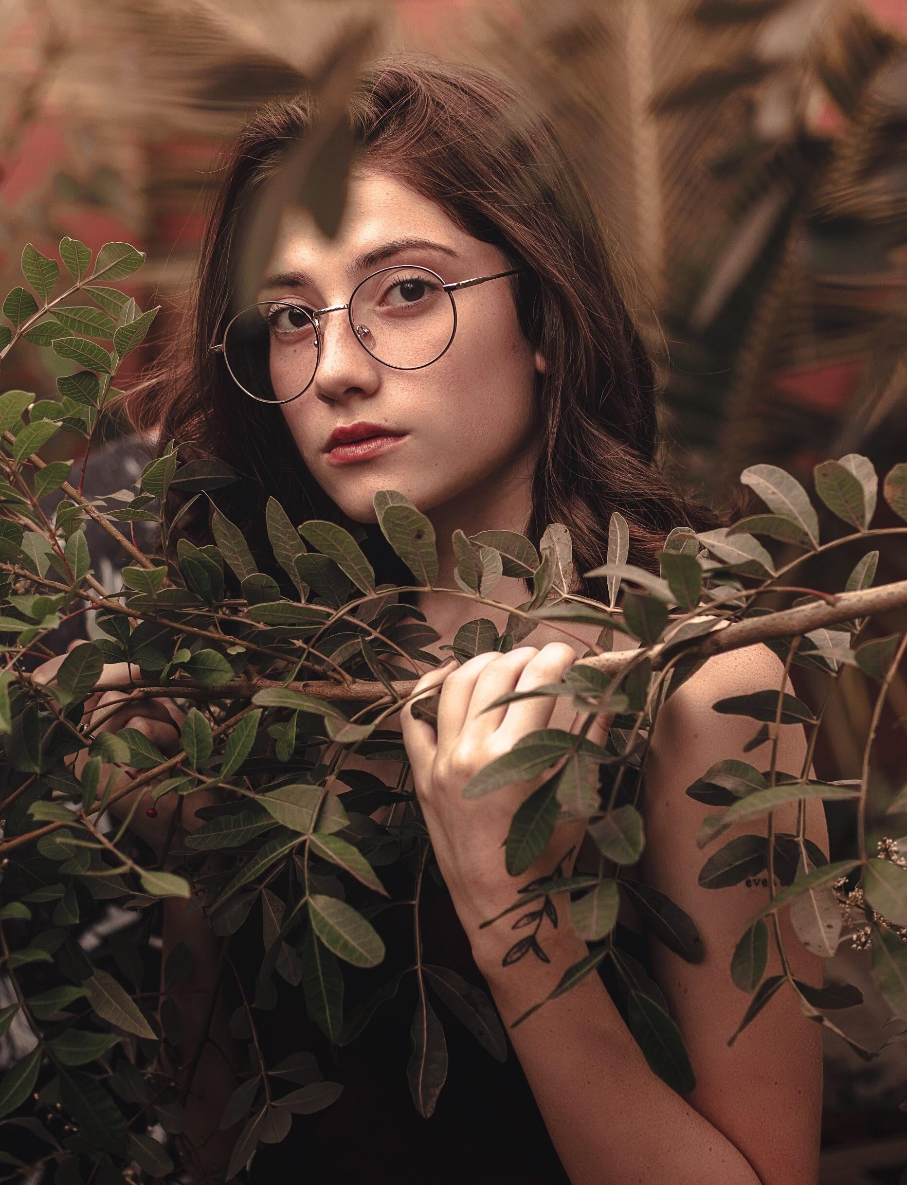 Woman Wearing Gray Eyeglasses Holding Tree