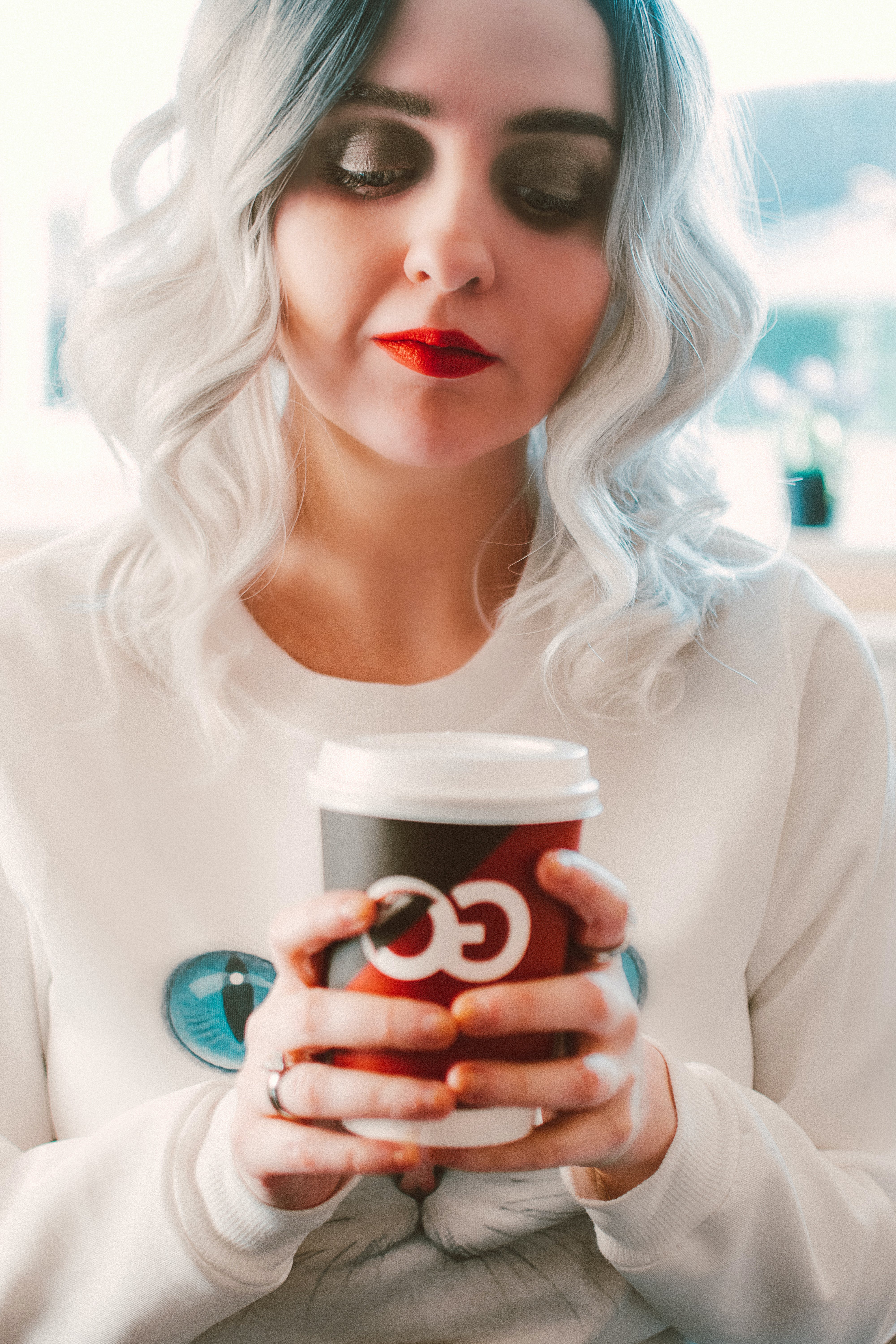Woman Wearing White Crew-neck Sweater Holding White Go Disposable Cup