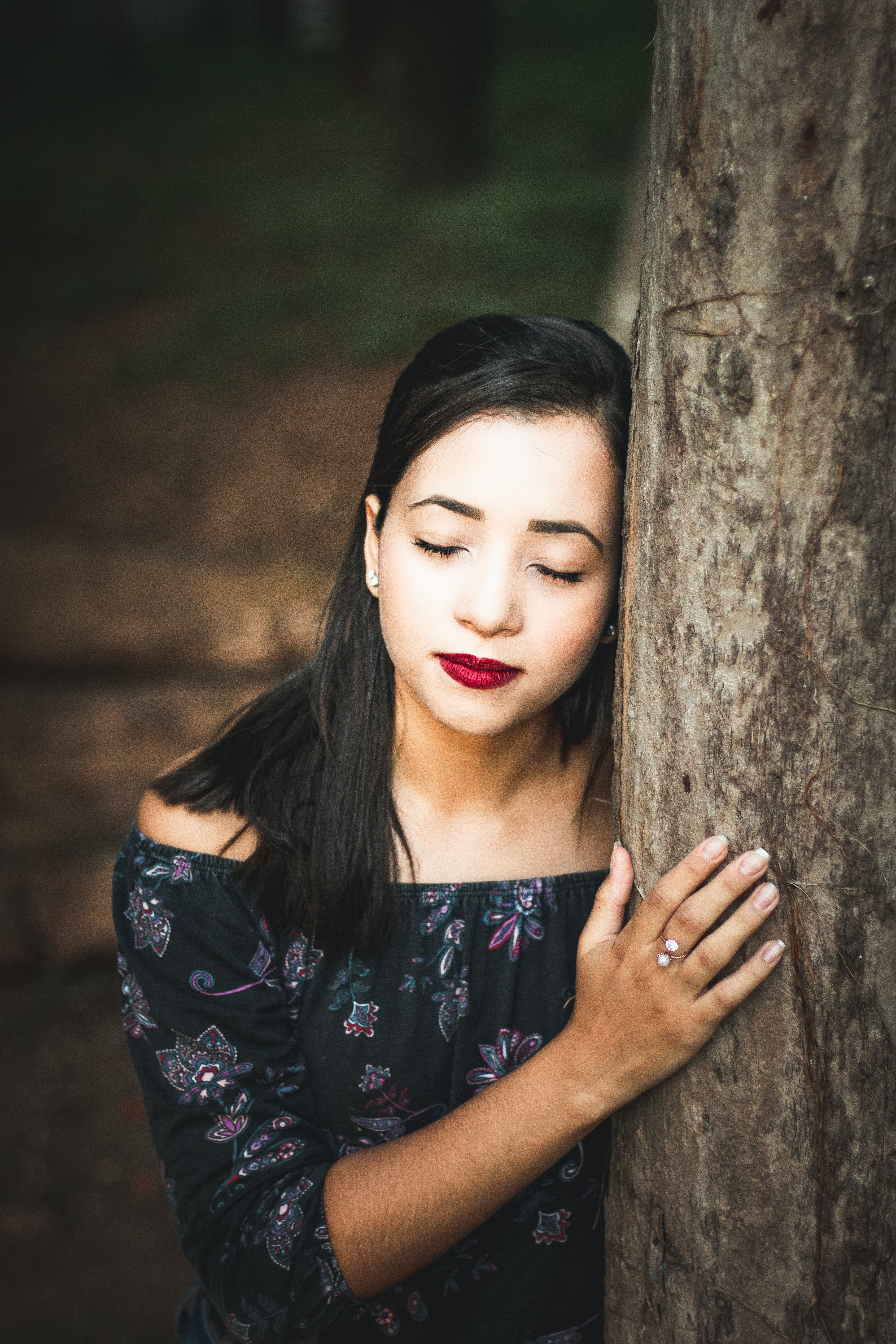 Woman Wearing Black Floral Off-shoulder Top Leaning on Tree Trunk