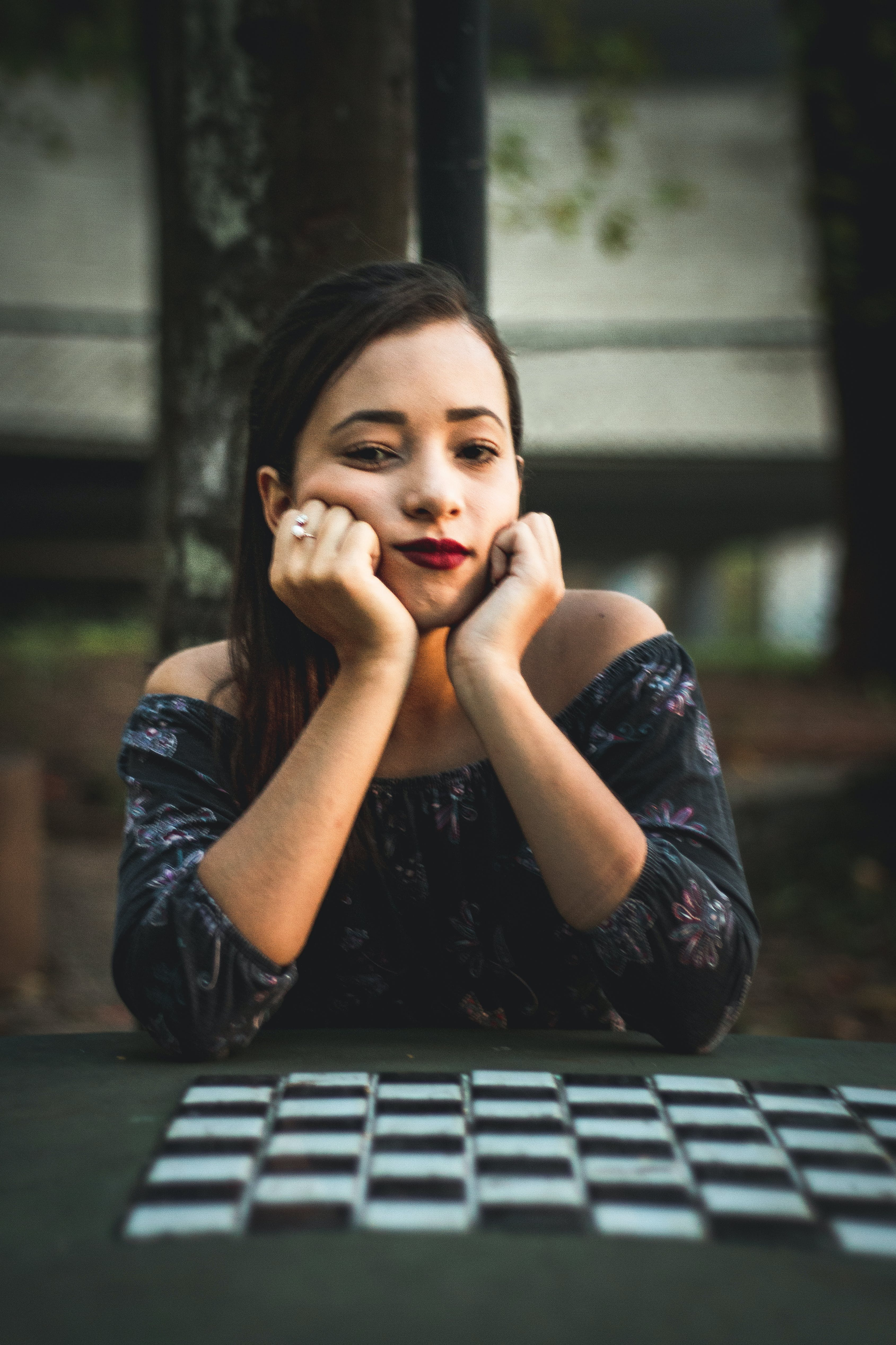 Woman Sitting Beside Chess Table With Hands on Chin