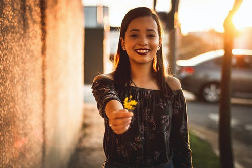 Smiling Woman Holding Yellow Petaled Flower